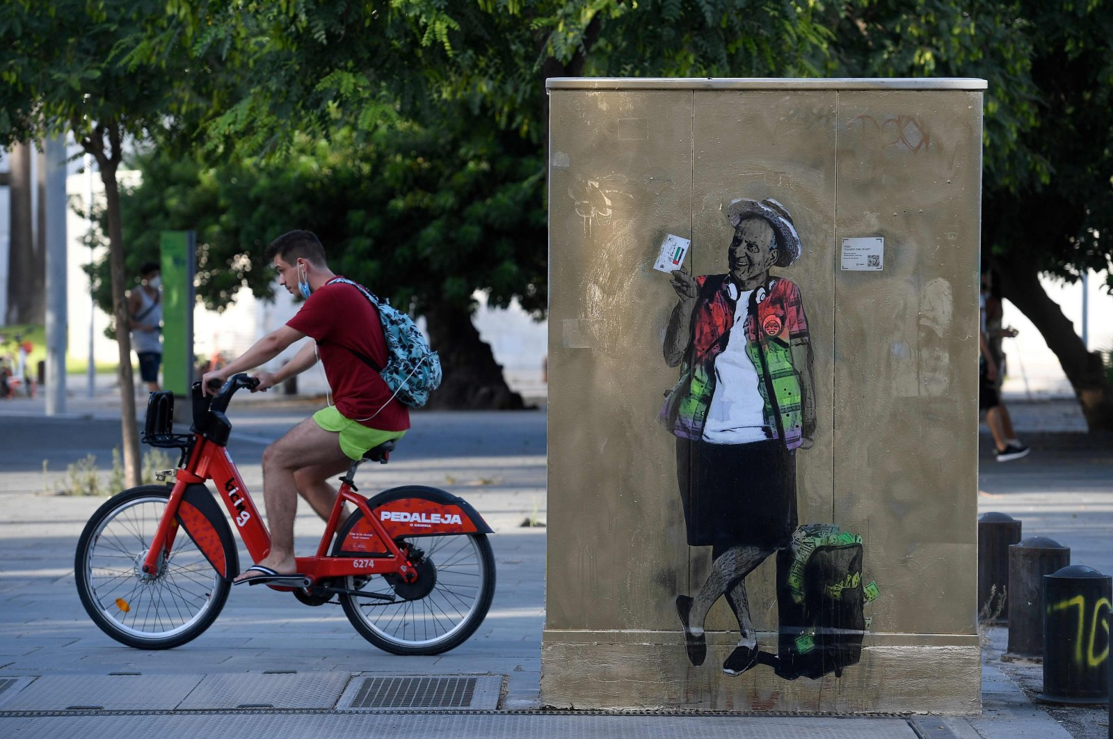 """A man rides a bicycle past street art by TVBoy titled """"Viajando como un Rey"""" (Travelling like a King) depicting former Spanish King Juan Carlos, in Barcelona, Spain, Aug. 20, 2020. (Photo by Josep Lago via AFP)"""