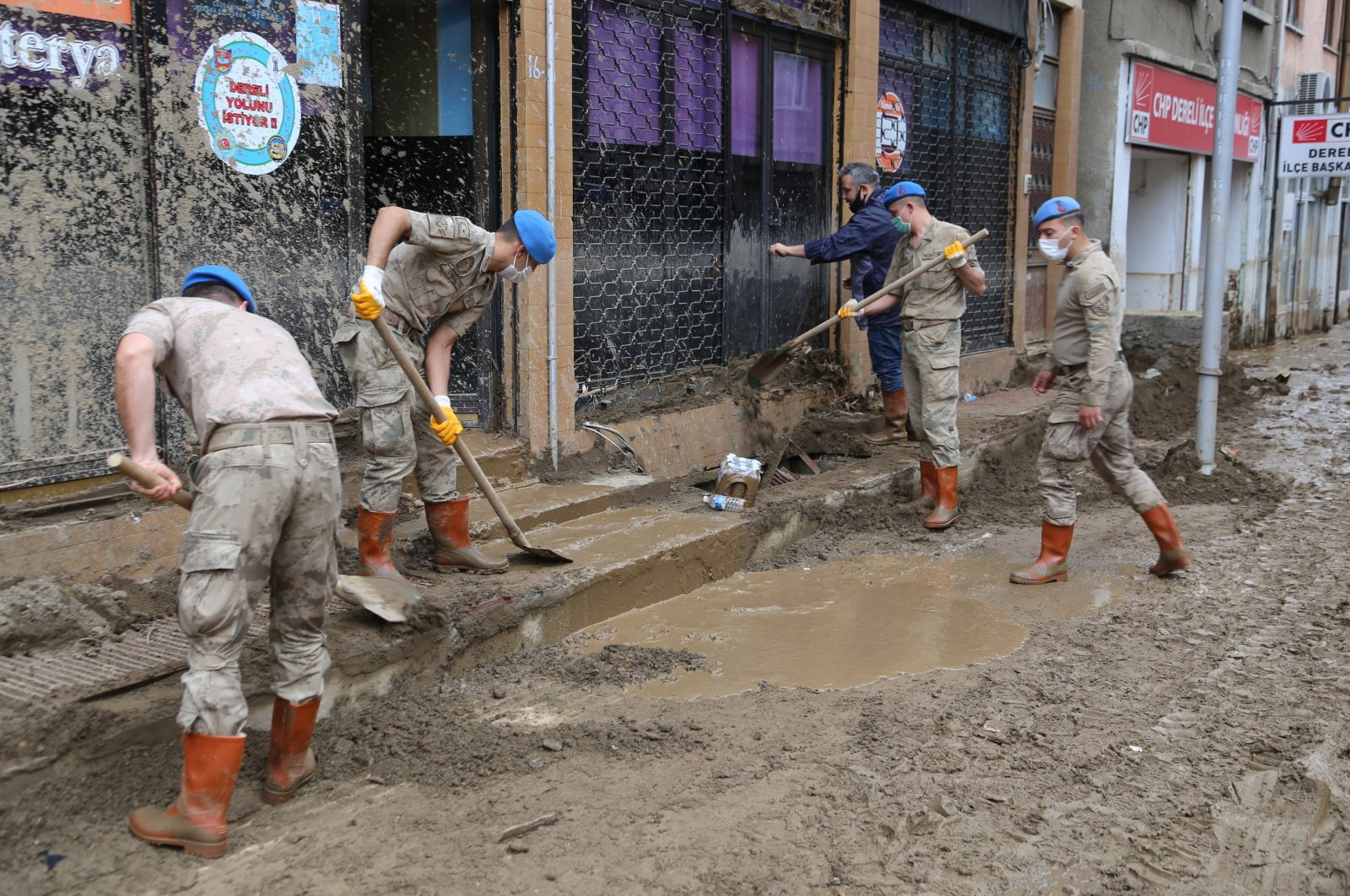Soldiers help clean the mud in front of a shop in Dereli district, in Giresun, northern Turkey, Aug. 27, 2020. (AA Photo)