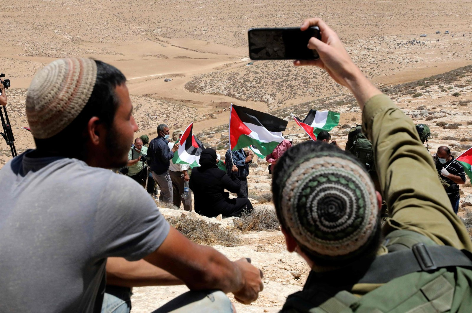 An Israeli soldier takes a selfie of himself with a Jewish settler, as Palestinian landowners and demonstrators protest Israeli settlement building activities on their land in al-Thaalaba village, near Yatta, south of Hebron city in the occupied West Bank, Aug. 21, 2020. (AFP Photo)