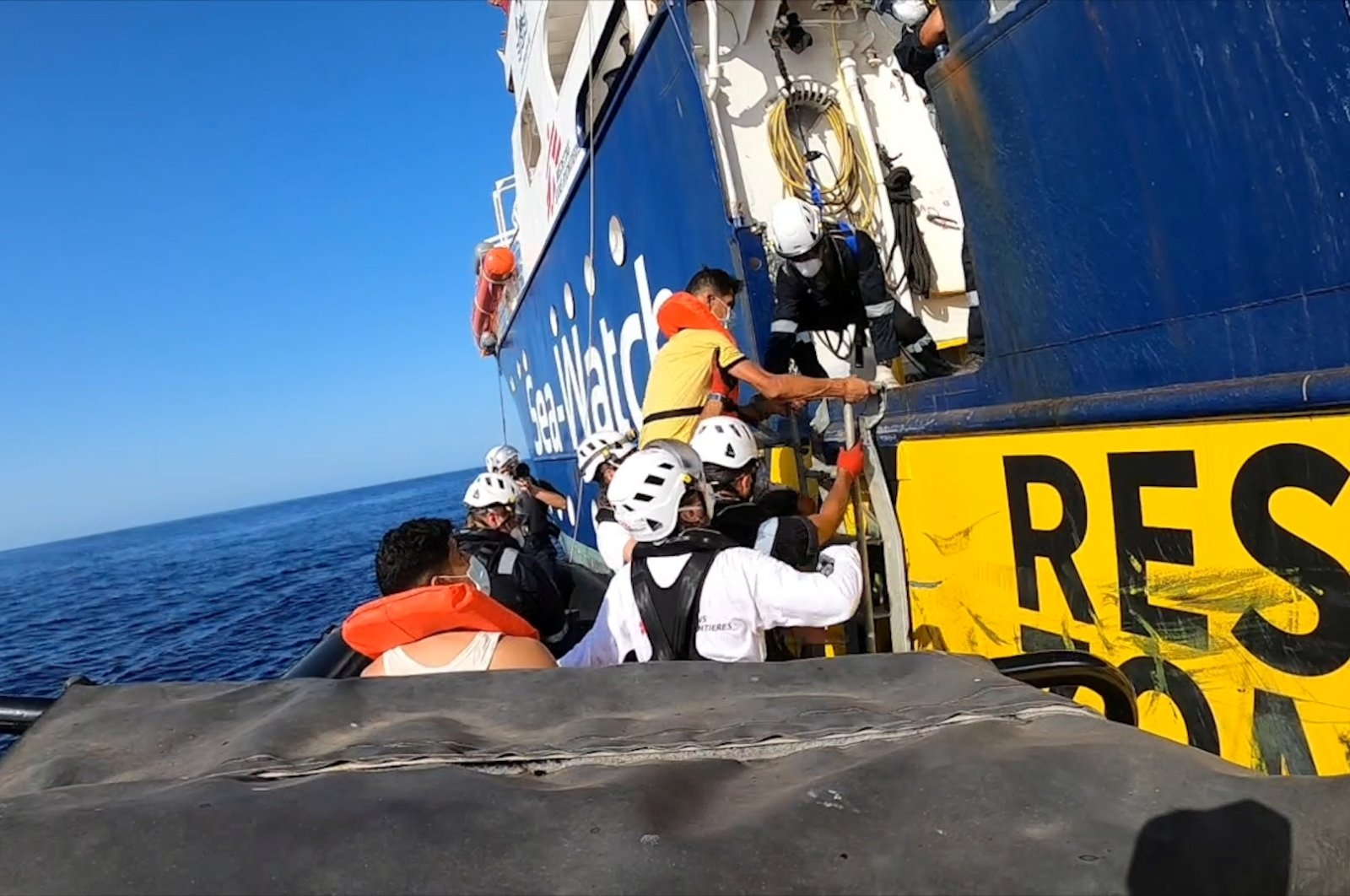 A rescued migrant enters the Sea-Watch 4 ship helped by a rescue team, at sea off the coast of Libya, Aug. 22, 2020, in this still image taken from the video. (Sea-Watch handout via Reuters Photo)