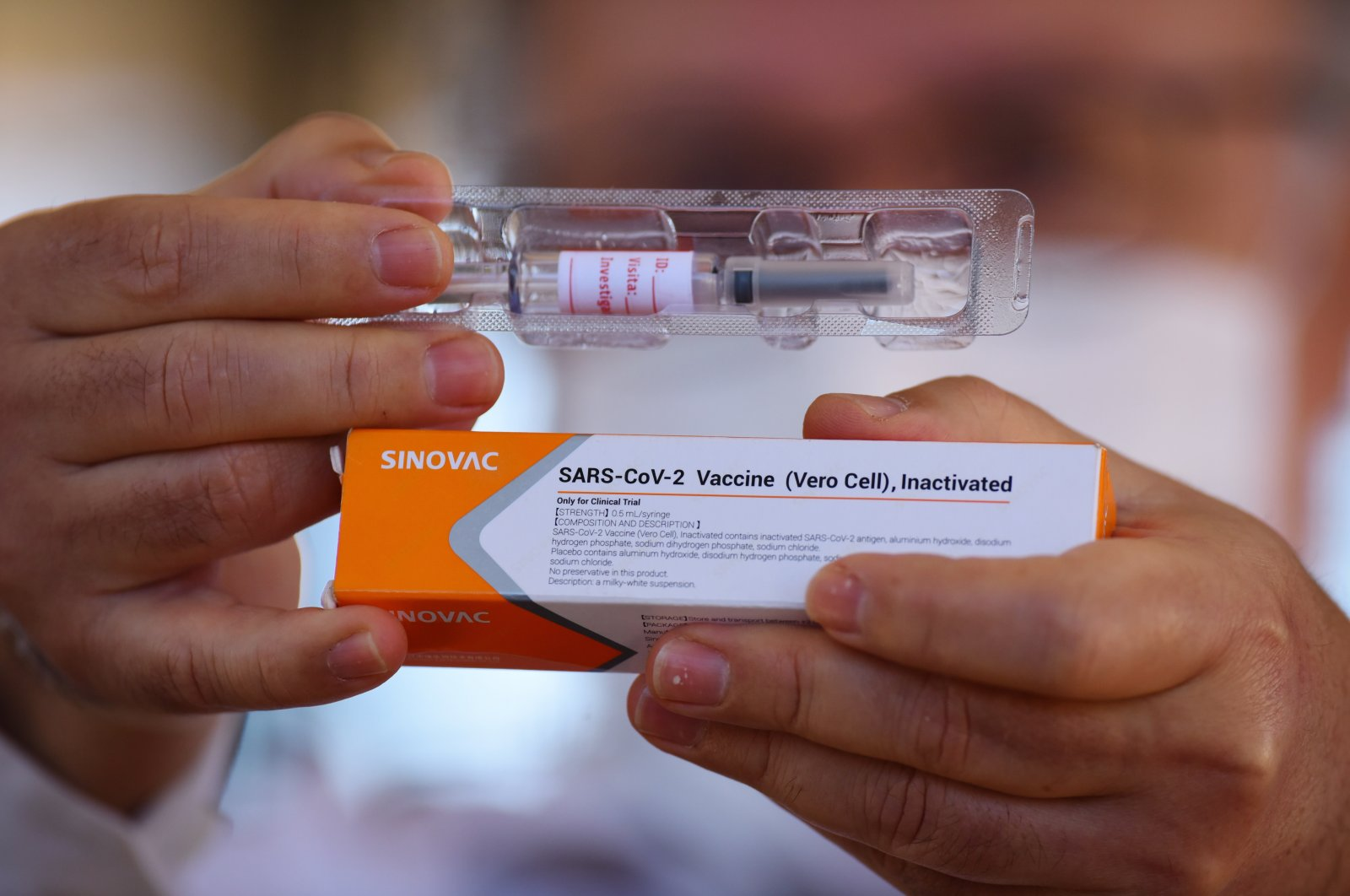 Professor Gustavo Romero, who coordinates research on the coronavirus vaccine in Brazil, shows a dose of Sinovac's coronavirus vaccine in a phase three trial at the University Hospital of Brasilia, in Brasilia, Brazil, Aug. 5, 2020. (EPA Photo)