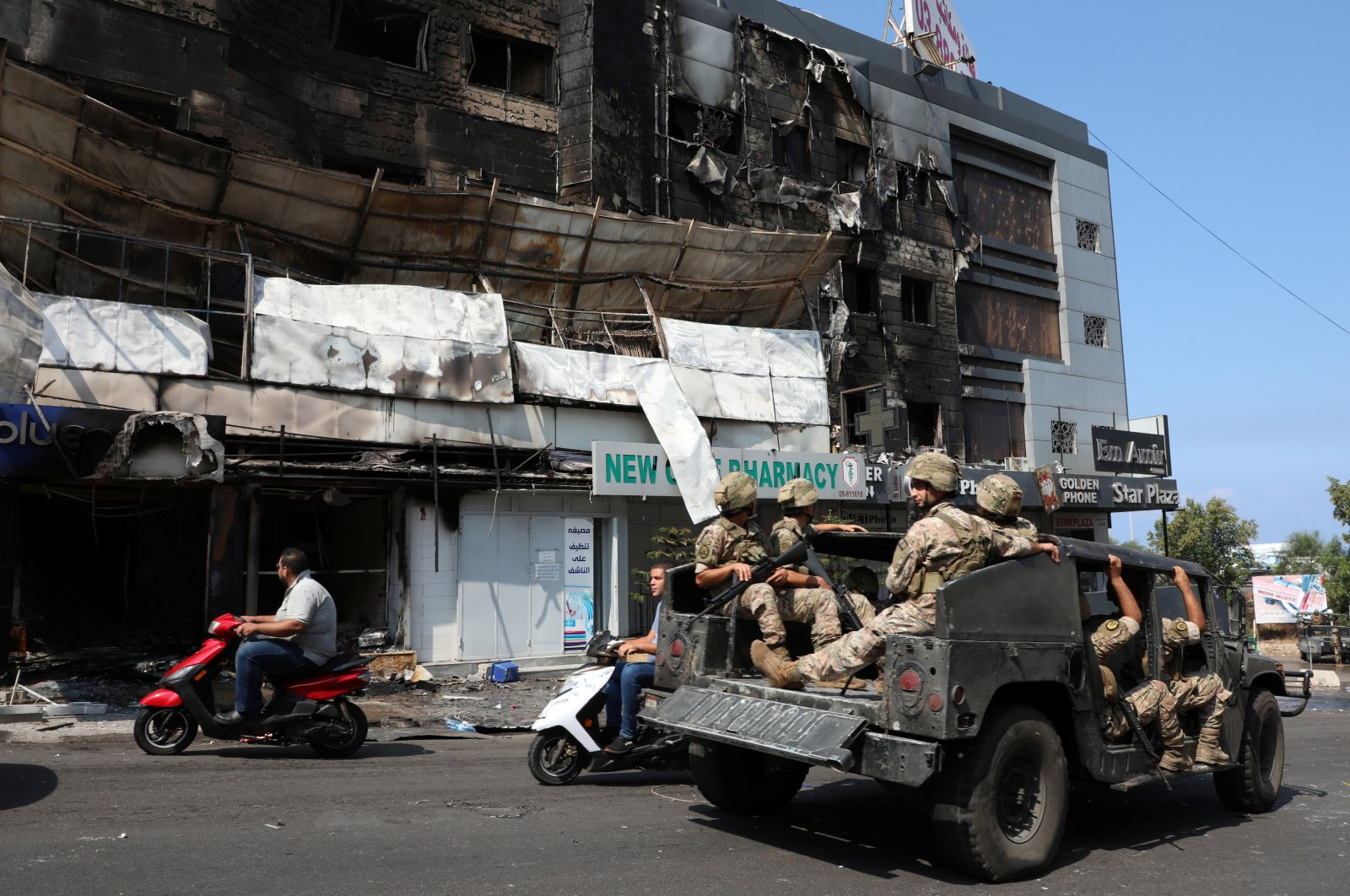 Lebanese soldiers patrol near burnt shops in the aftermath of clashes, Khaldeh, Lebanon, Aug. 28, 2020. (Reuters Photo)