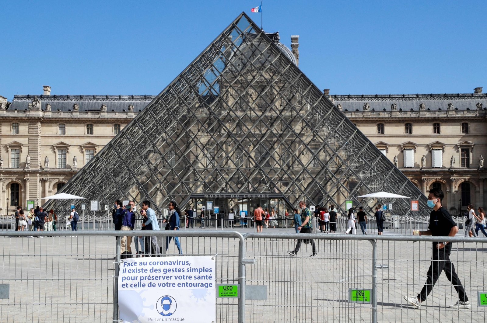 People wearing face masks walk in front of the Louvre Pyramid, Paris, France, Aug. 27, 2020. (AFP Photo)
