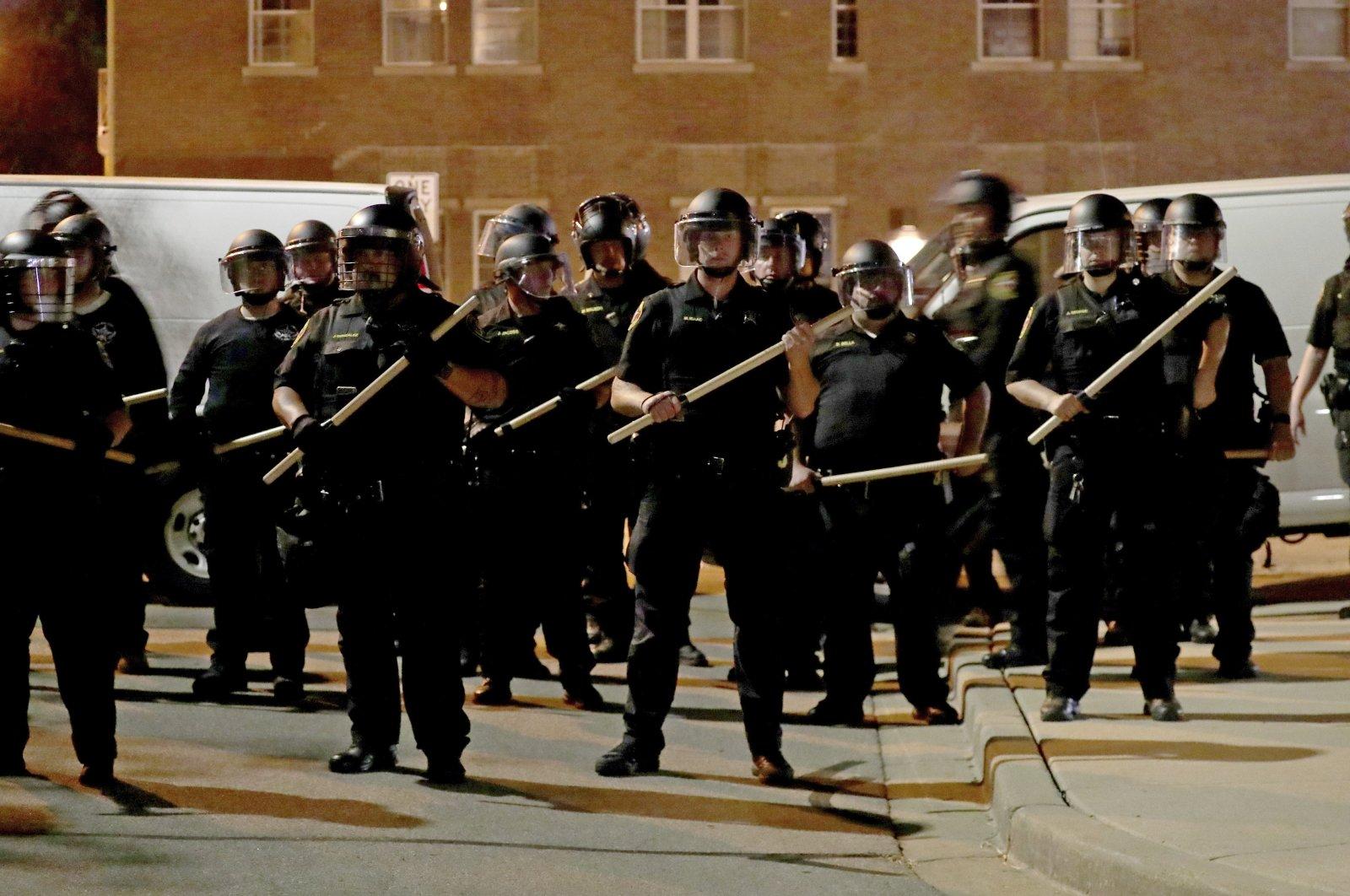Police in riot gear stand guard in Kenosha, Wisconsin, U.S., Aug. 23, 2020. (Milwaukee Journal-Sentinel via AP)
