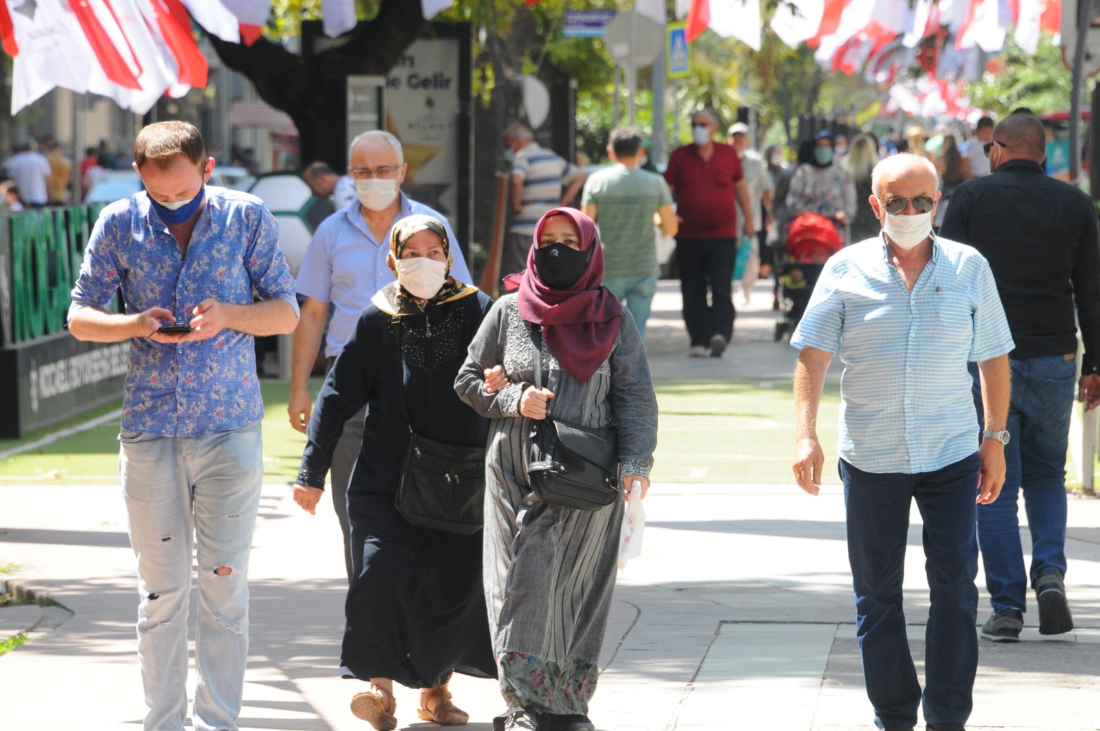 People wearing protective masks walk on a street in Kocaeli, northwestern Turkey, Aug. 26, 2020. (DHA Photo)