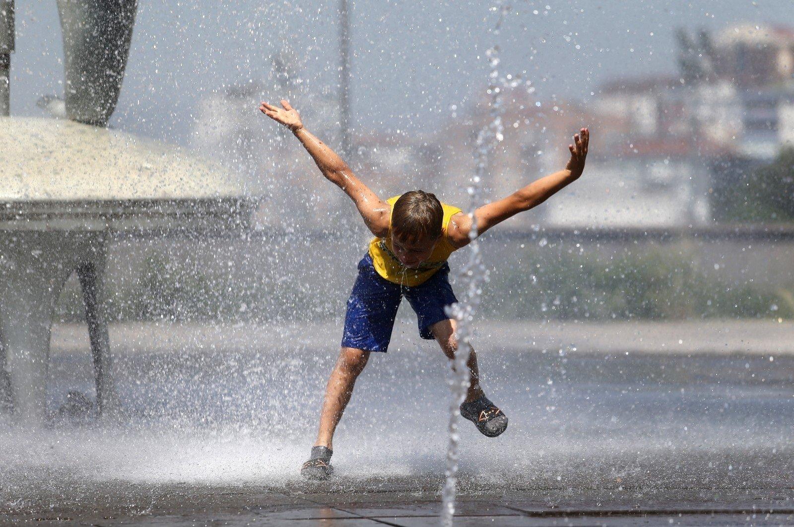 A boy leans toward a sprinkler to cool off in Bursa, northwestern Turkey, Aug. 25, 2020. (İHA Photo)