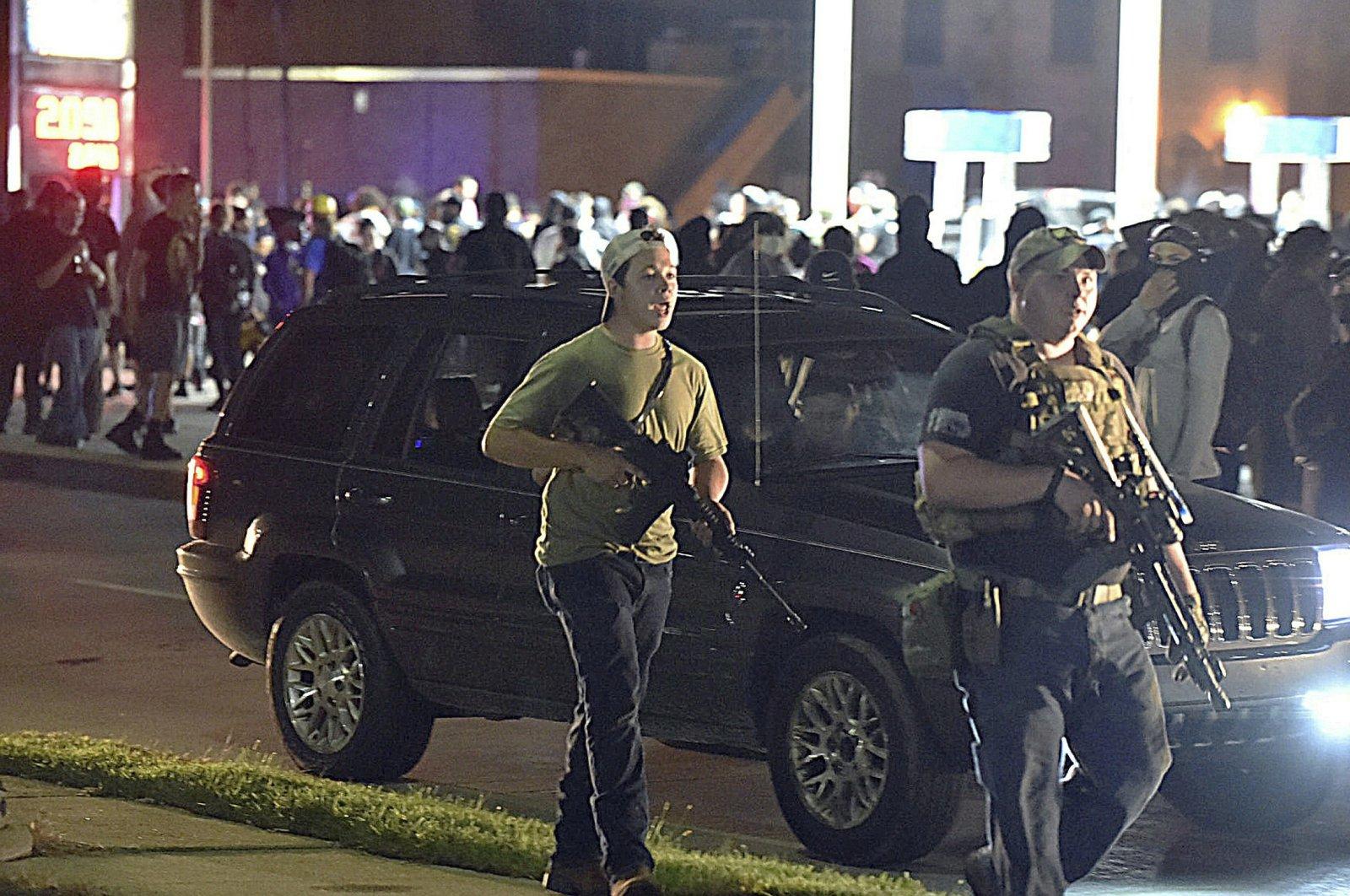 Kyle Rittenhouse (L) walks with another armed civilian, Kenosha, Wis., Aug. 25, 2020. (AP Photo)