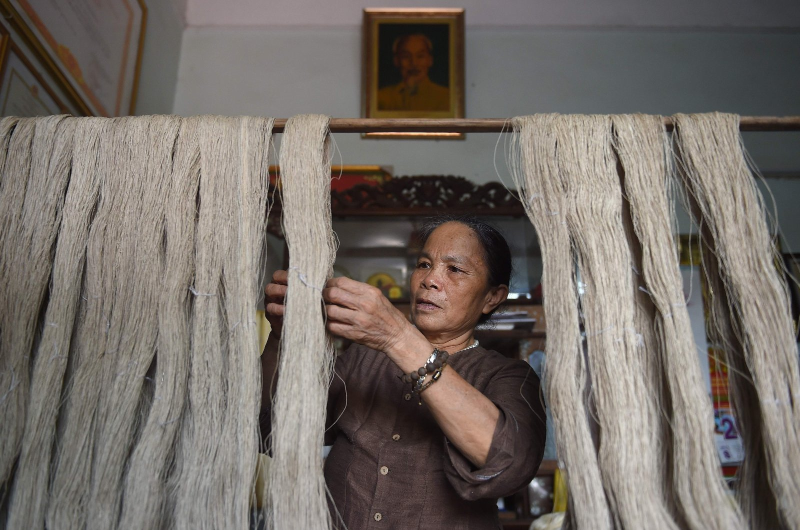 "Vietnamese weaver, Phan Thi Thuan checking lotus ""silk"" yarns at her workshop in Hanoi on Aug. 26, 2020. (Photo by Nhac NGUYEN / AFP)"