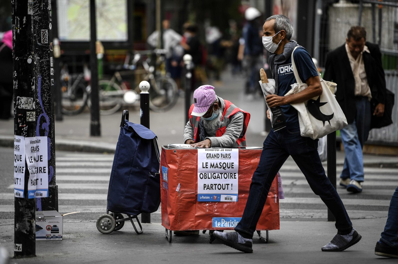 A placard hangs on the side of a newspaper stand reading, 'Paris The Mask Is Mandatory Everywhere' as the vendor wearing a protective face mask waits for customers in Paris on Aug. 28, 2020. (AFP Photo)