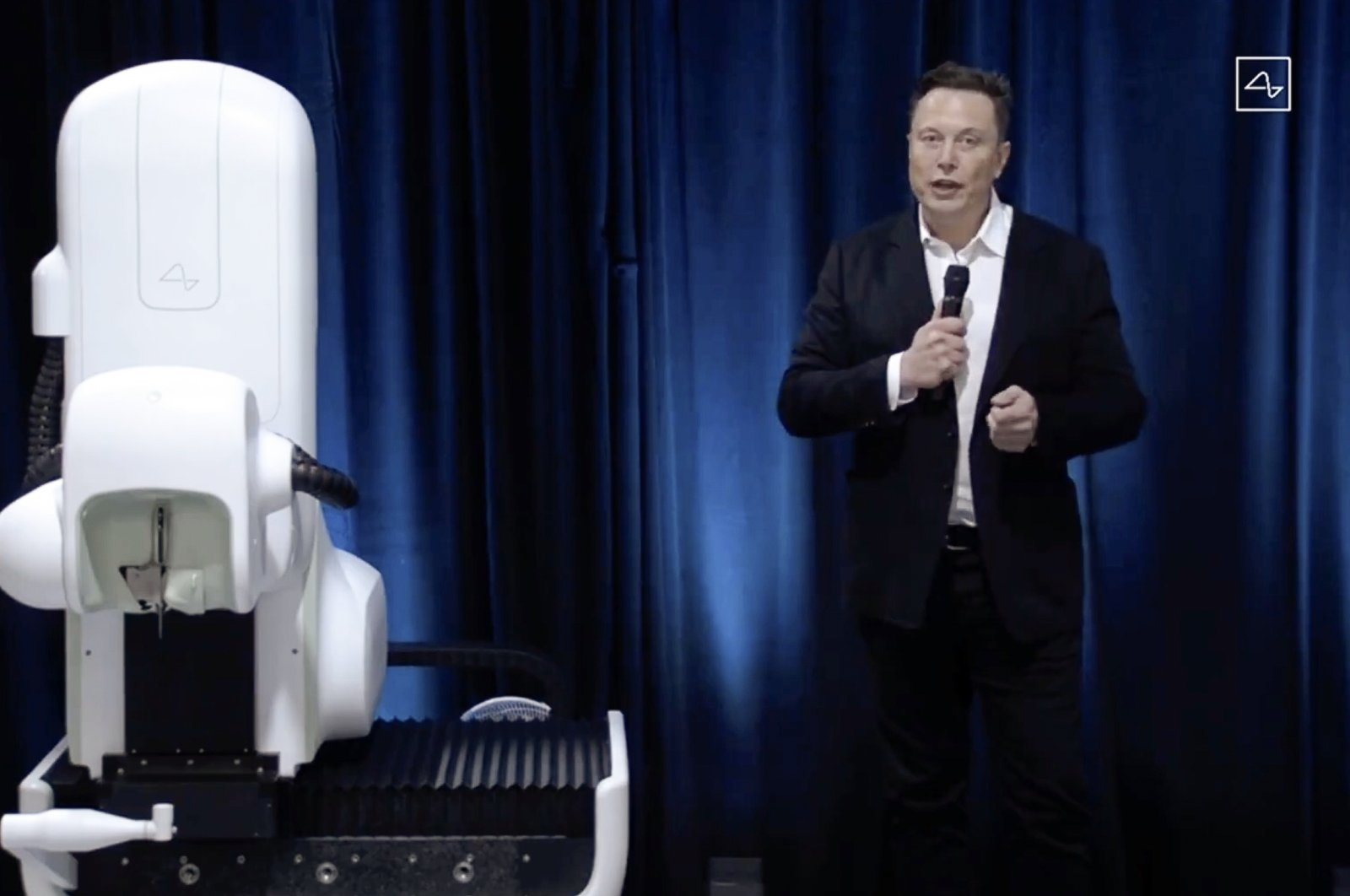 This video grab made from the online Neuralink livestream shows Elon Musk standing next to the surgical robot during his Neuralink presentation, Aug. 28, 2020. (AFP Photo/Neuralink)
