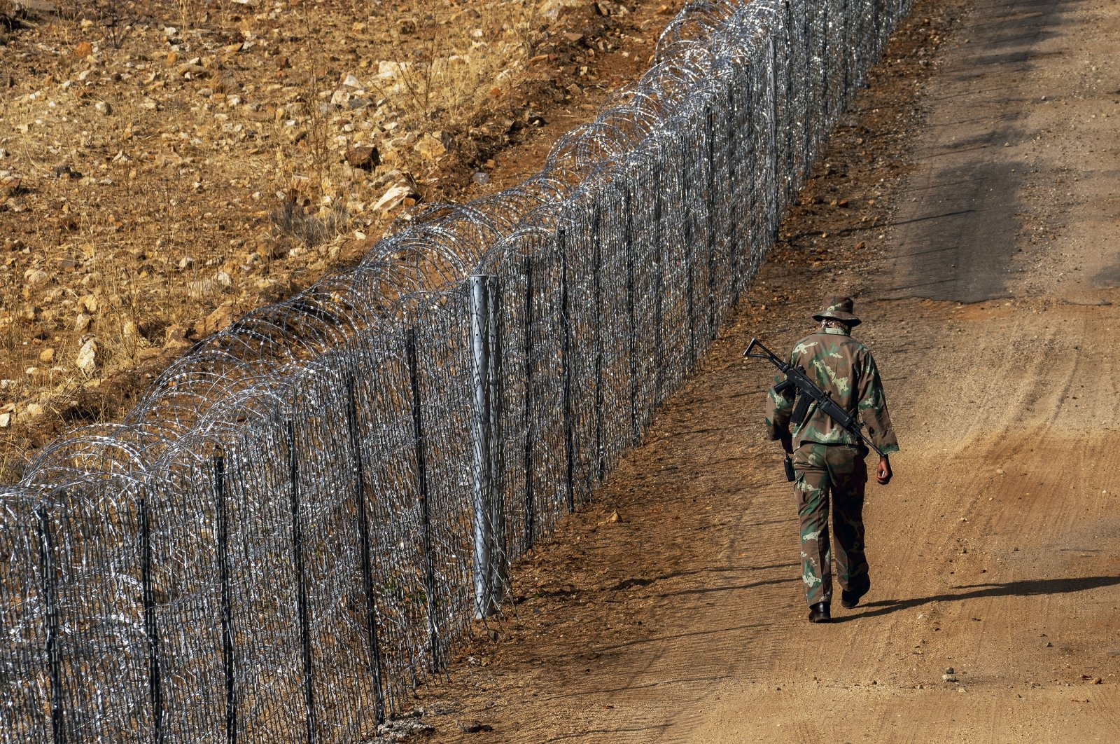 South Africa National Defense Forces soldier patrols along the newly built fence on the South Africa-Zimbabwe border near the border town of Musina, South Africa, June 30, 2020. (AP Photo)