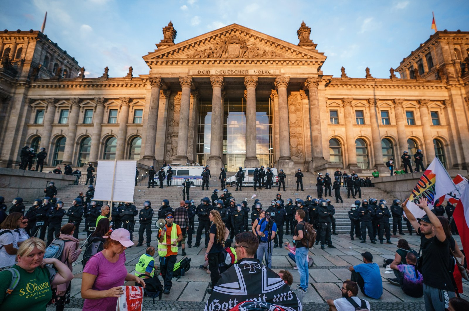 Riot police monitor the scene as right-wing protesters stand in the area in front of the Reichstag building, the seat of the German parliament Bundestag, which was cleared by police after right-wing protesters tried to climb the stairs and enter the building following a protest against government-imposed coronavirus regulations, in Berlin, Germany, Aug. 29, 2020. (EPA Photo)