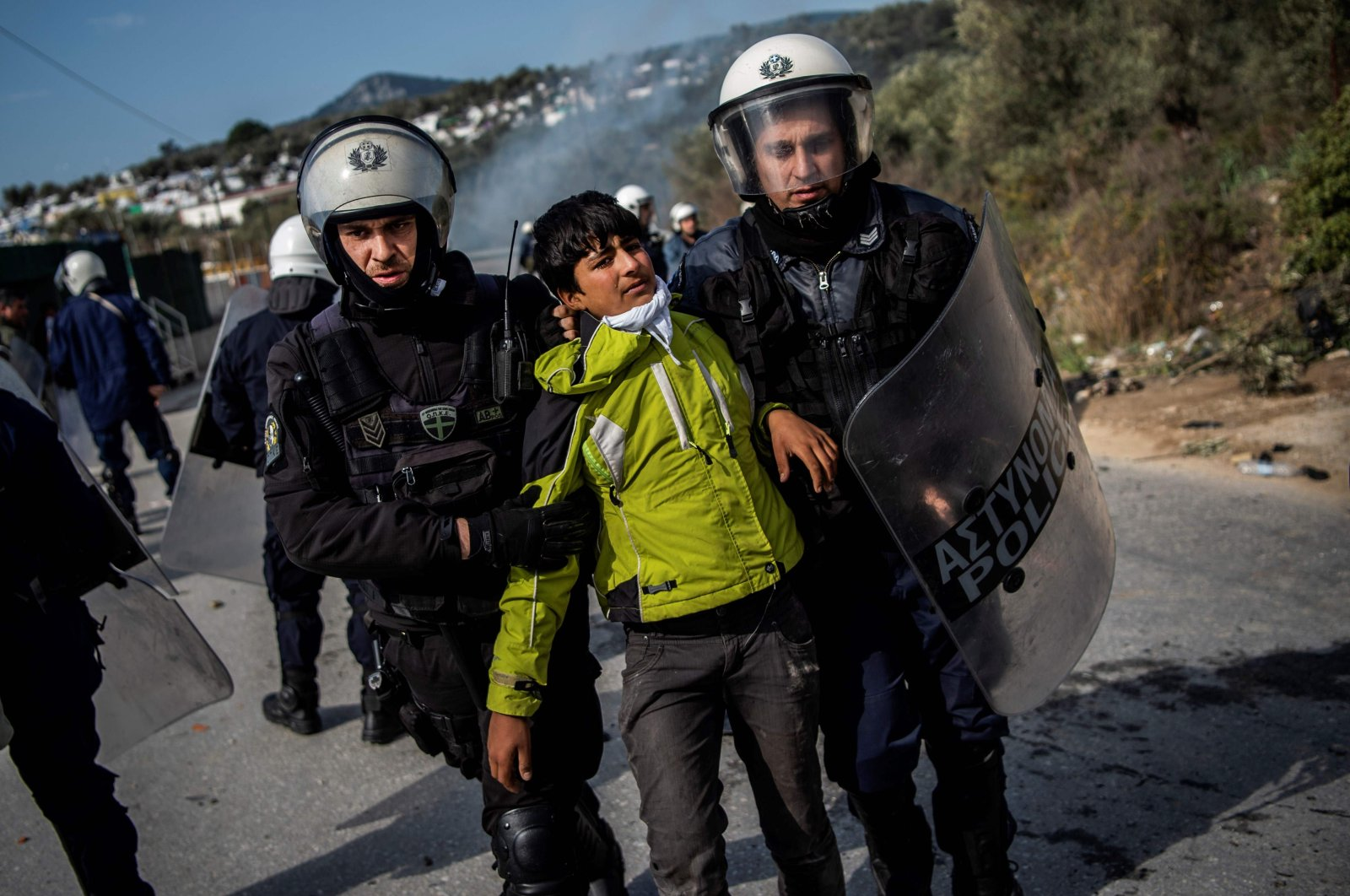 Riot police detain a migrant during clashes near the Moria camp for refugees and migrants, on the island of Lesbos, on March 2, 2020. (AFP Photo)