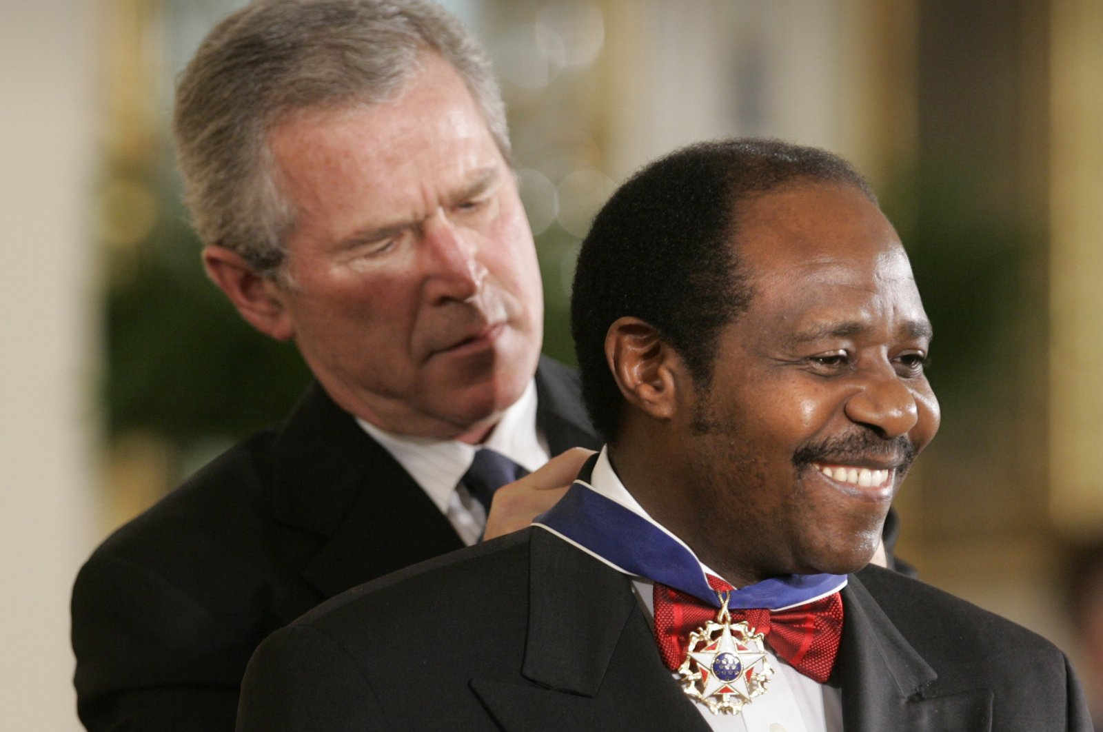 President Bush awards Paul Rusesabagina, who sheltered people at a hotel he managed during the 1994 Rwandan genocide, the Presidential Medal of Freedom Award in the East Room of the White House, in Washington D.C., Nov. 9, 2005. (AP Photo)
