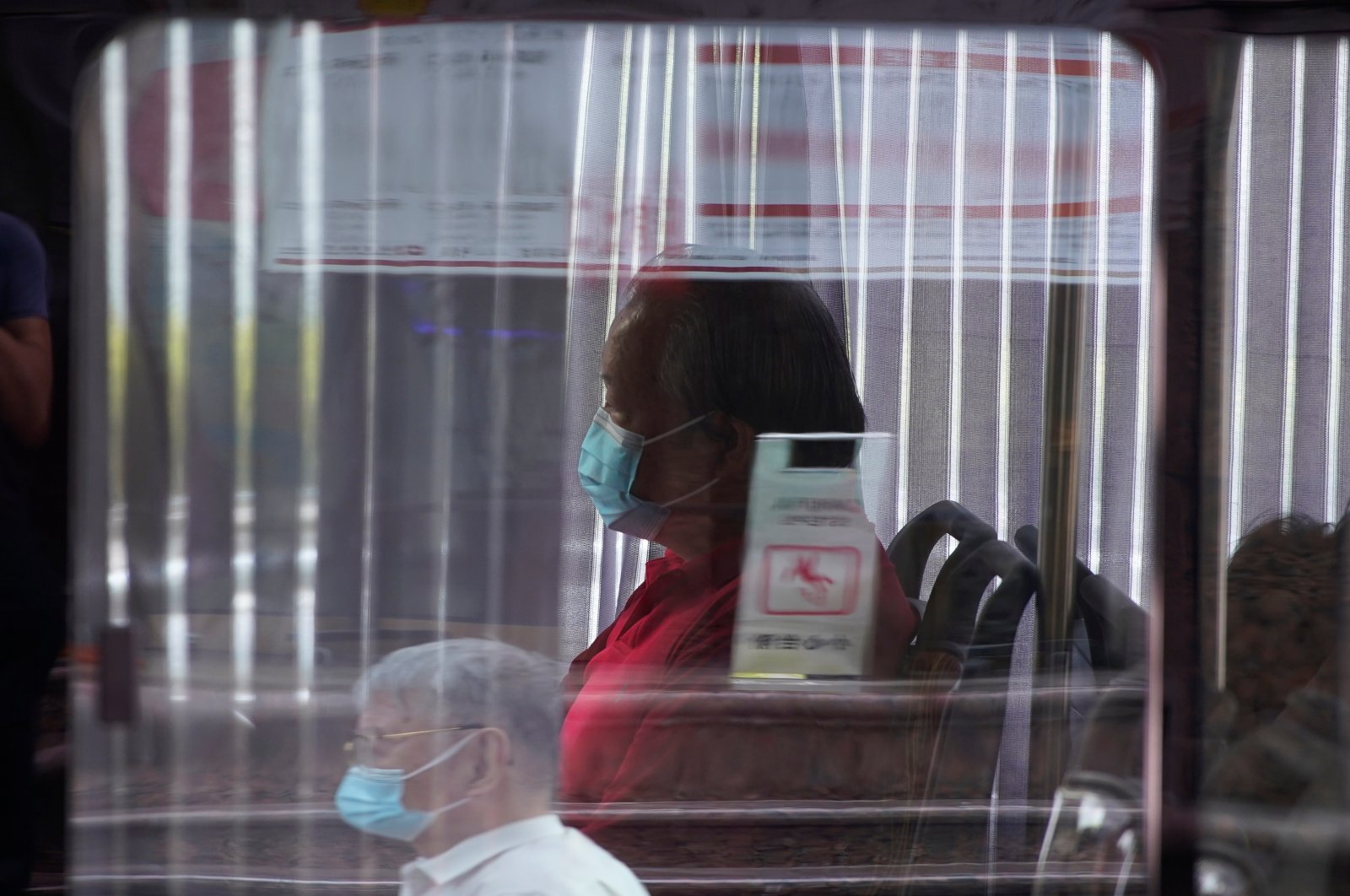 A man wearing a face mask sits on a bus amid the coronavirus disease (COVID-19) outbreak, in Shanghai, China, Aug. 27, 2020. (Reuters Photo)