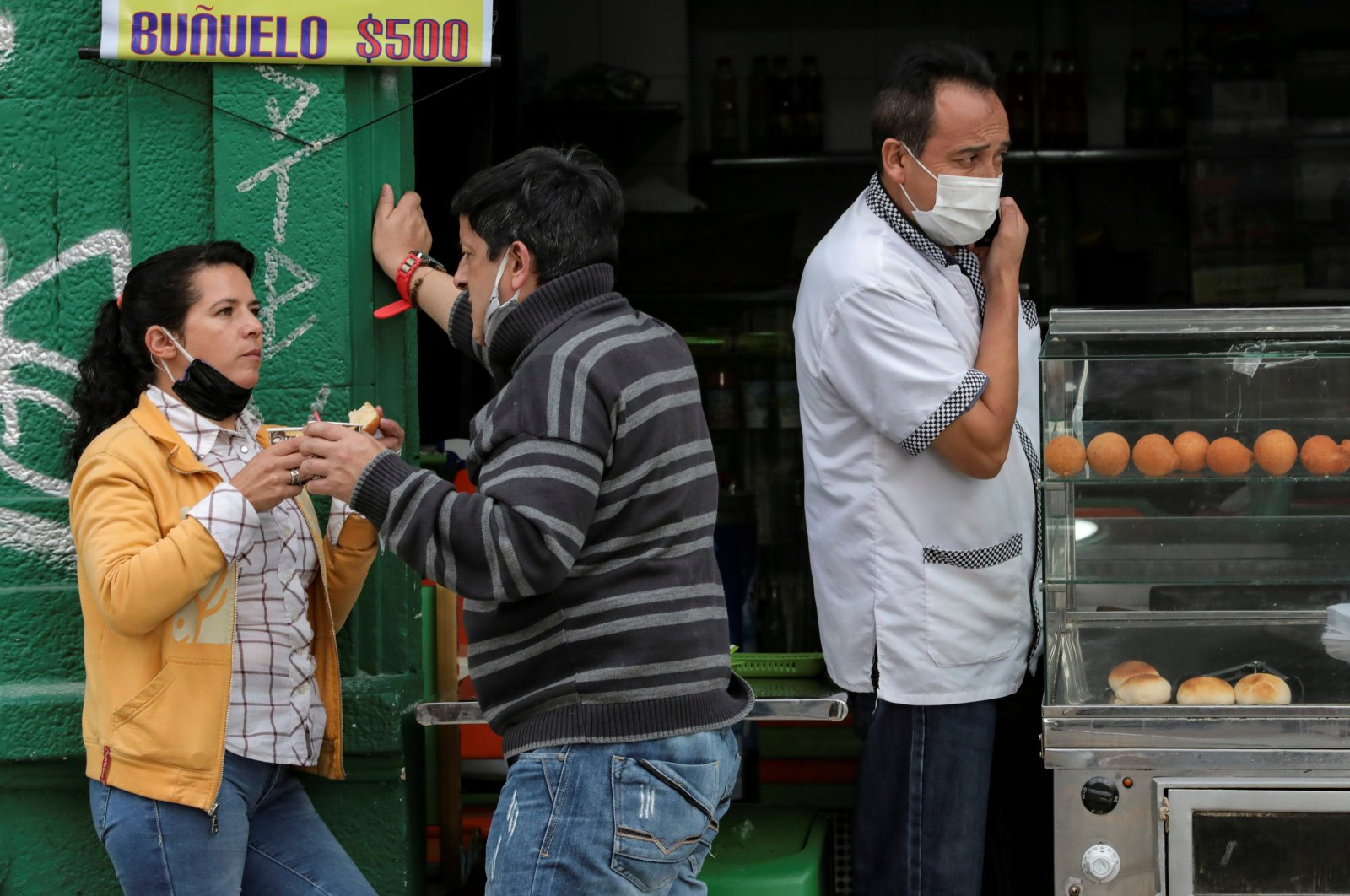 People with face masks converse outside a cafeteria during the government-mandated quarantine to lower the rates of contagion from the coronavirus outbreak, in Bogota, Colombia, July 27, 2020. (Reuters Photo)