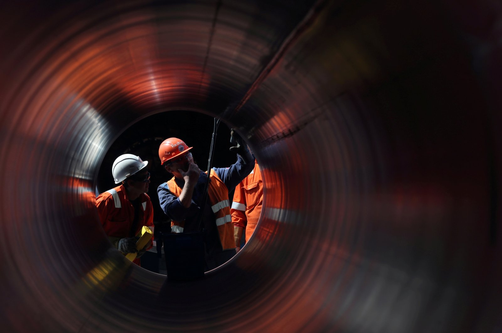 Workers are seen through a pipe at the construction site of the Nord Stream 2 gas pipeline, near the town of Kingisepp, Leningrad region, Russia, June 5, 2019. (Reuters Photo)