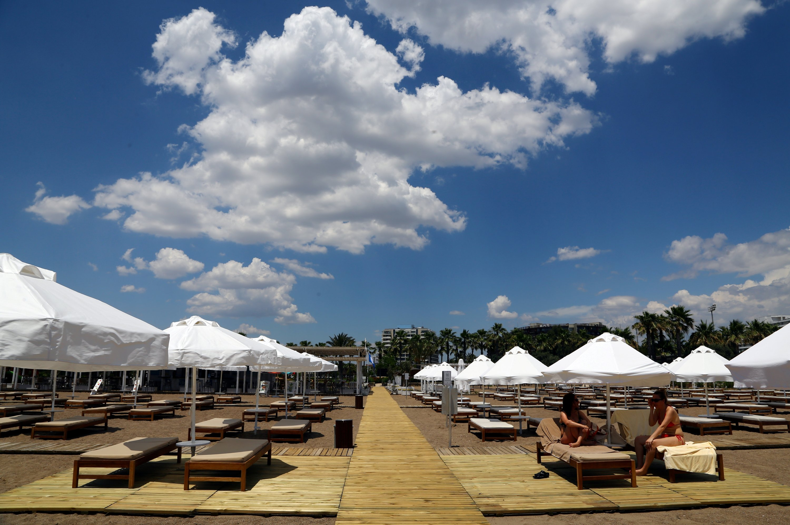 Women chat under umbrellas at the beach of Lara Barut Collection Hotel, amid the COVID-19 outbreak, in the southern resort city of Antalya, Turkey, June 19, 2020. (Reuters Photo)