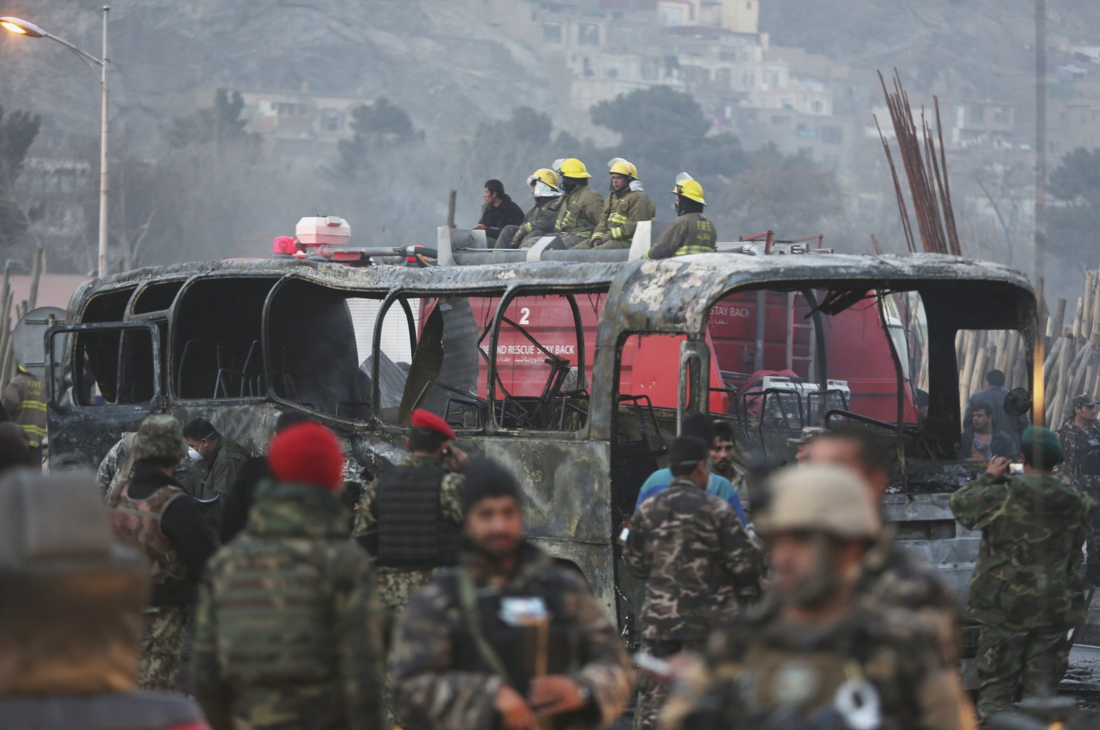 Afghan security personnel inspect a damaged bus at the site of a suicide attack by the Taliban in Kabul, Afghanistan, Dec. 13, 2014. (AP Photo)