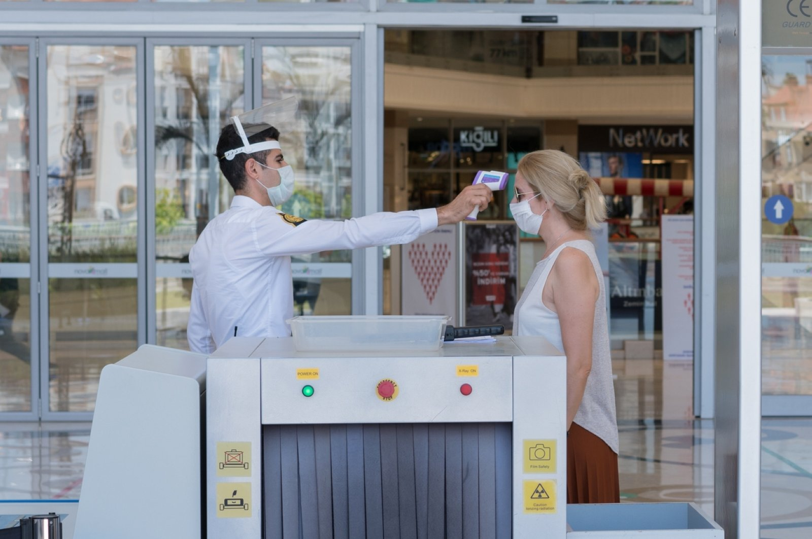 A shopping mall worker checks the temperature of a customer as a precaution against the coronavirus pandemic, Antalya, southern Turkey, June 8, 2020. (iStock Photo by Mustafa Gül)