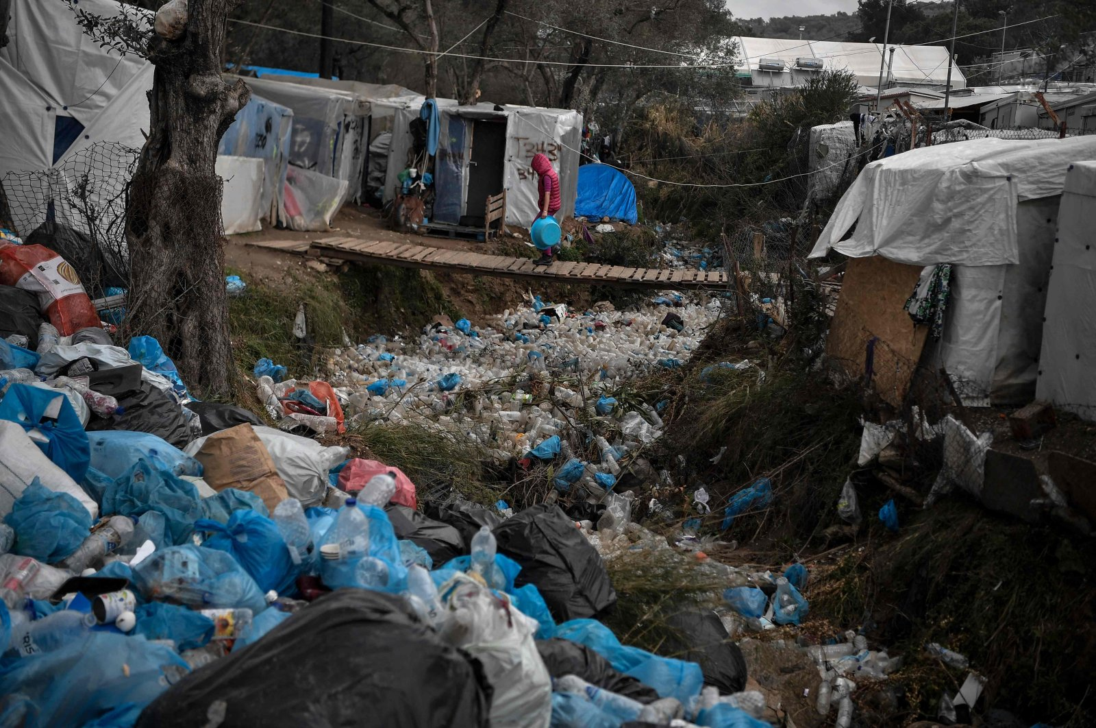 A child walks on a bridge over a trash-filled ditch in the overcrowded Moria migrant camp on the Greek Aegean island of Lesbos, March 5, 2020. (AFP Photo)