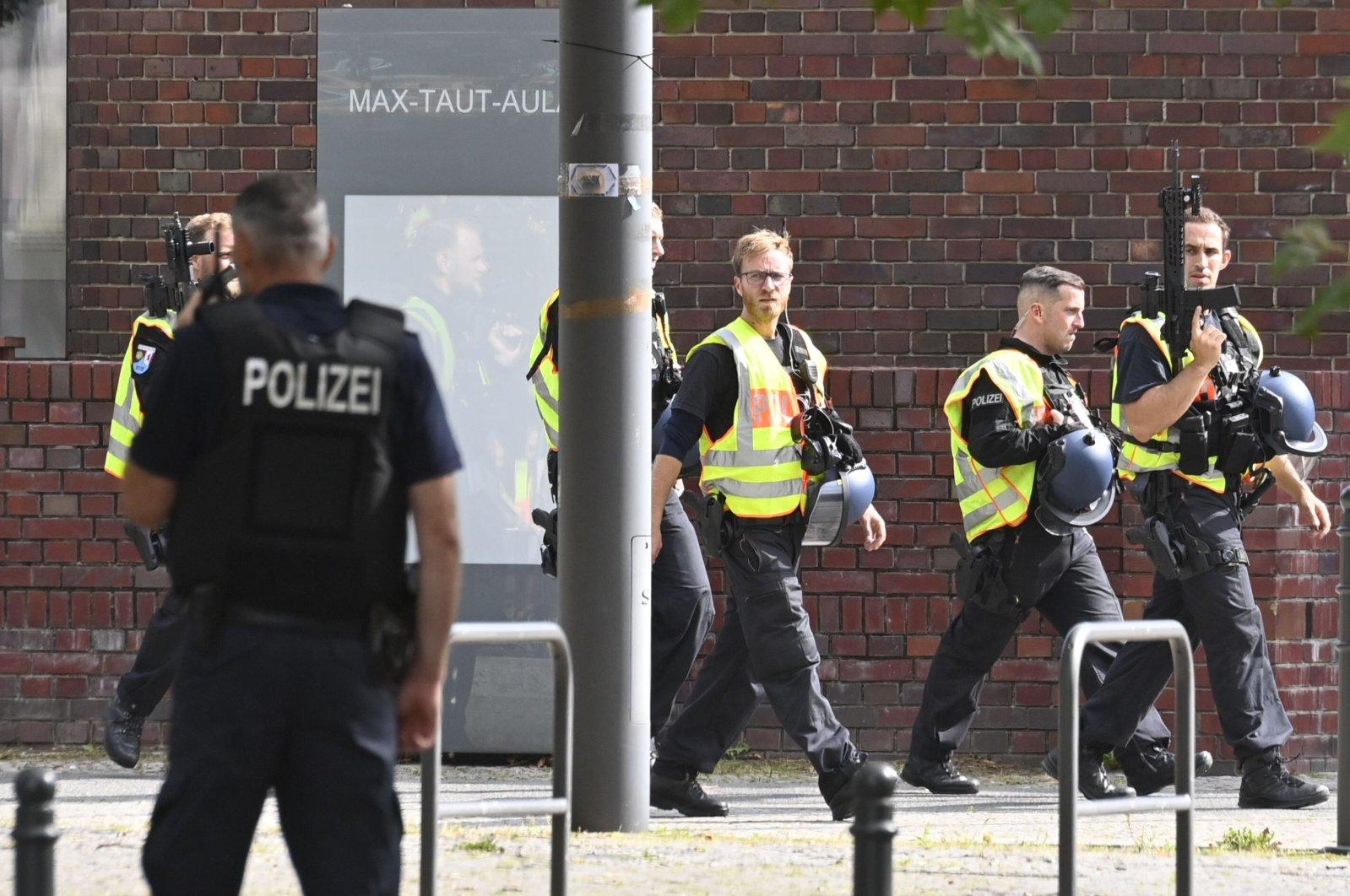 German armed policemen walk past a school in Berlin's Rummelsburg district, Germany, Aug. 28, 2020. (AFP Photo)
