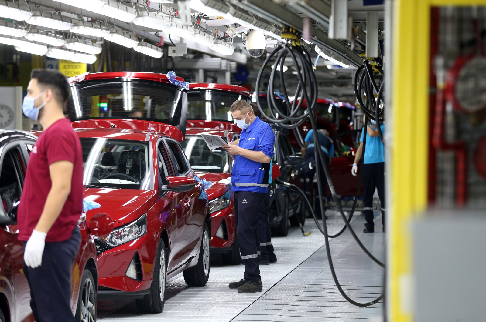 Workers are seen beside new i20 model cars at Hyundai Assan's Izmit factory in northwestern Kocaeli, Turkey, Aug. 28, 2020.