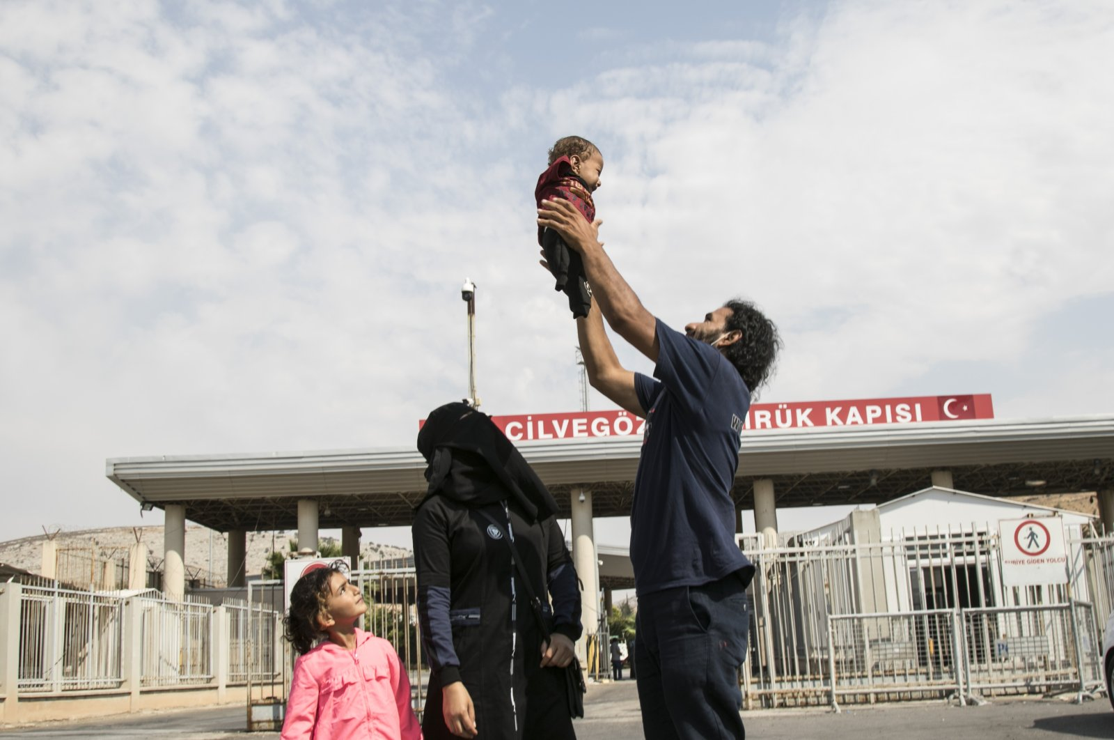 Khaled Misaytif holds his boy Muhammad as the family arrives at the Cilvegözü border crossing in Hatay, southern Turkey, Sept. 1, 2020. (AA Photo)