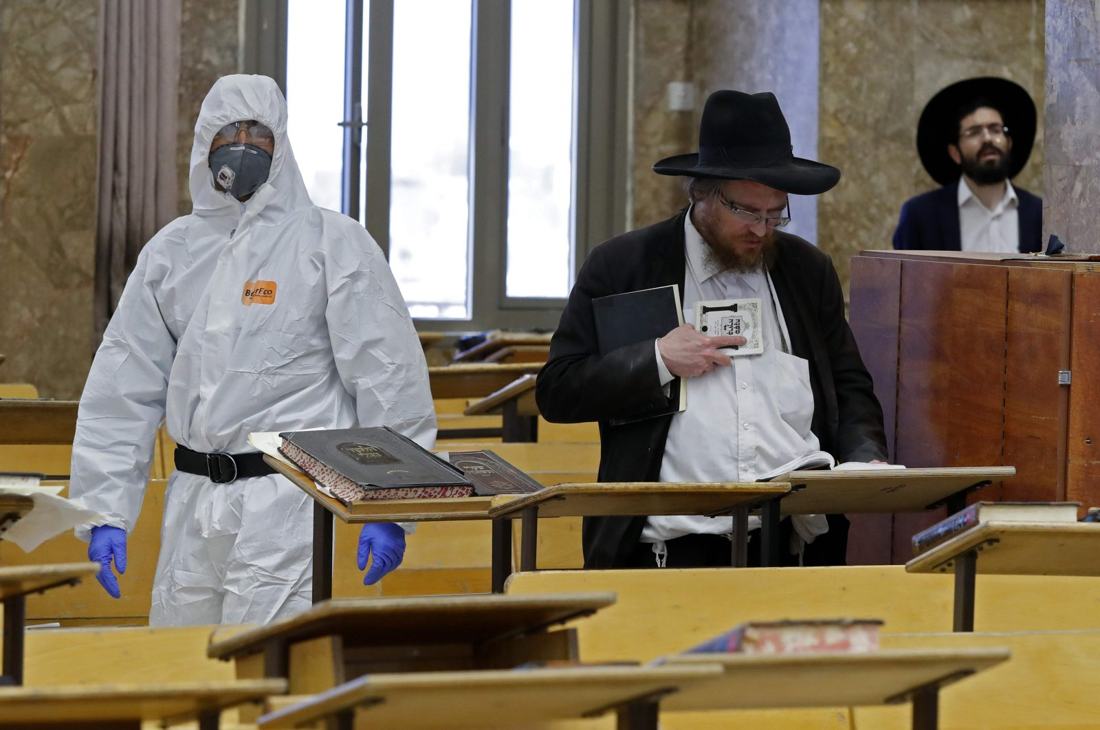 In this file photo, an Israeli police officer, dressed in a protective outfit, enters a yeshiva (a Jewish educational institution for studies of traditional religious texts) in the Israeli city of Bnei Brak during a check to ensure that social distancing measures imposed by Israeli authorities meant to curb the spread of the coronavirus are being followed, April 2, 2020. (AFP Photo)