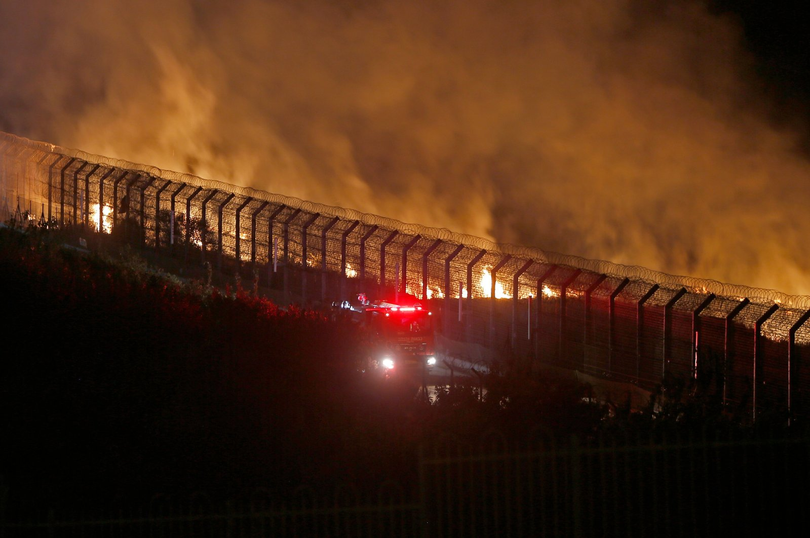 Israeli firefighters battle a blaze on the border fence with Syria, near the Druze village of Majdal Shams in the Israel-annexed Golan Heights, Aug. 31, 2020. (AFP Photo)