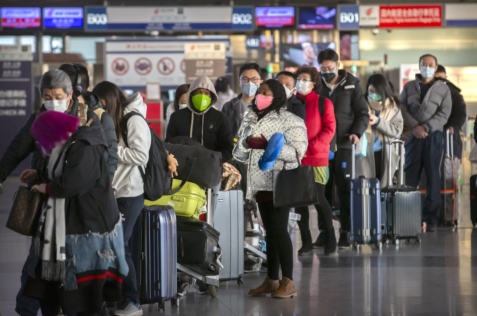 Travelers wearing face masks line up to check in for a flight at Beijing Capital International Airport in Beijing, Jan. 30, 2020. (AP Photo)