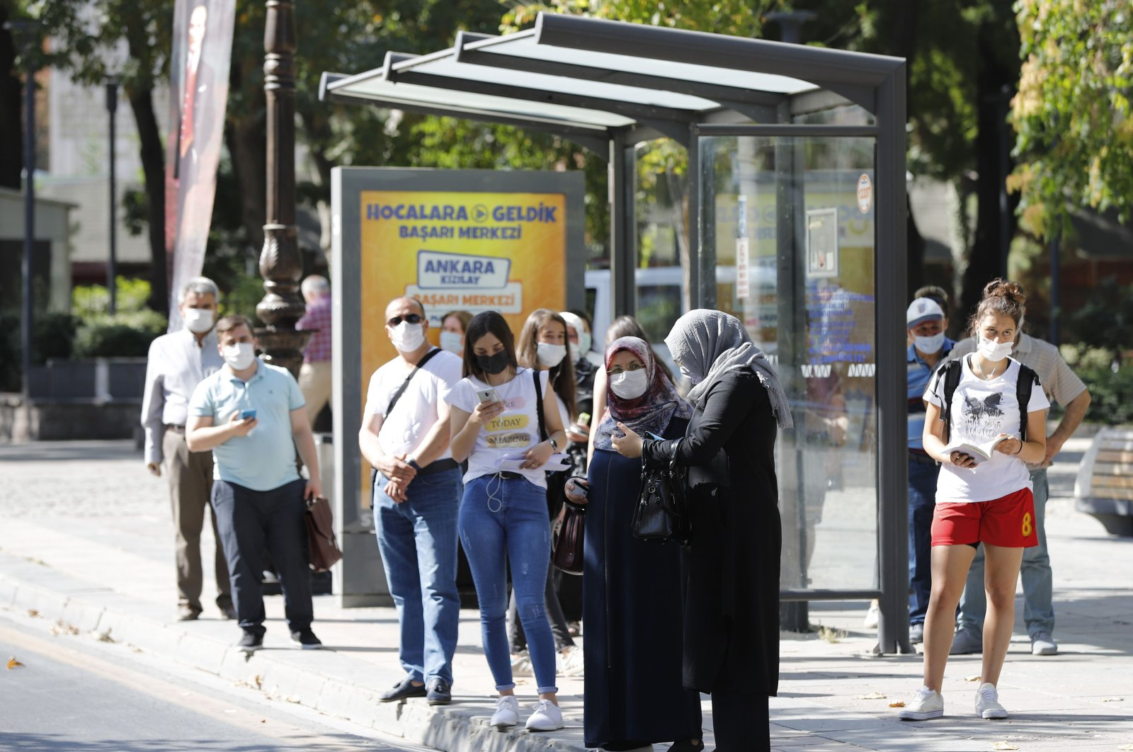 People wearing protective masks wait at a bus stop, in the capital Ankara, Turkey, Sept. 3, 2020. (DHA Photo)