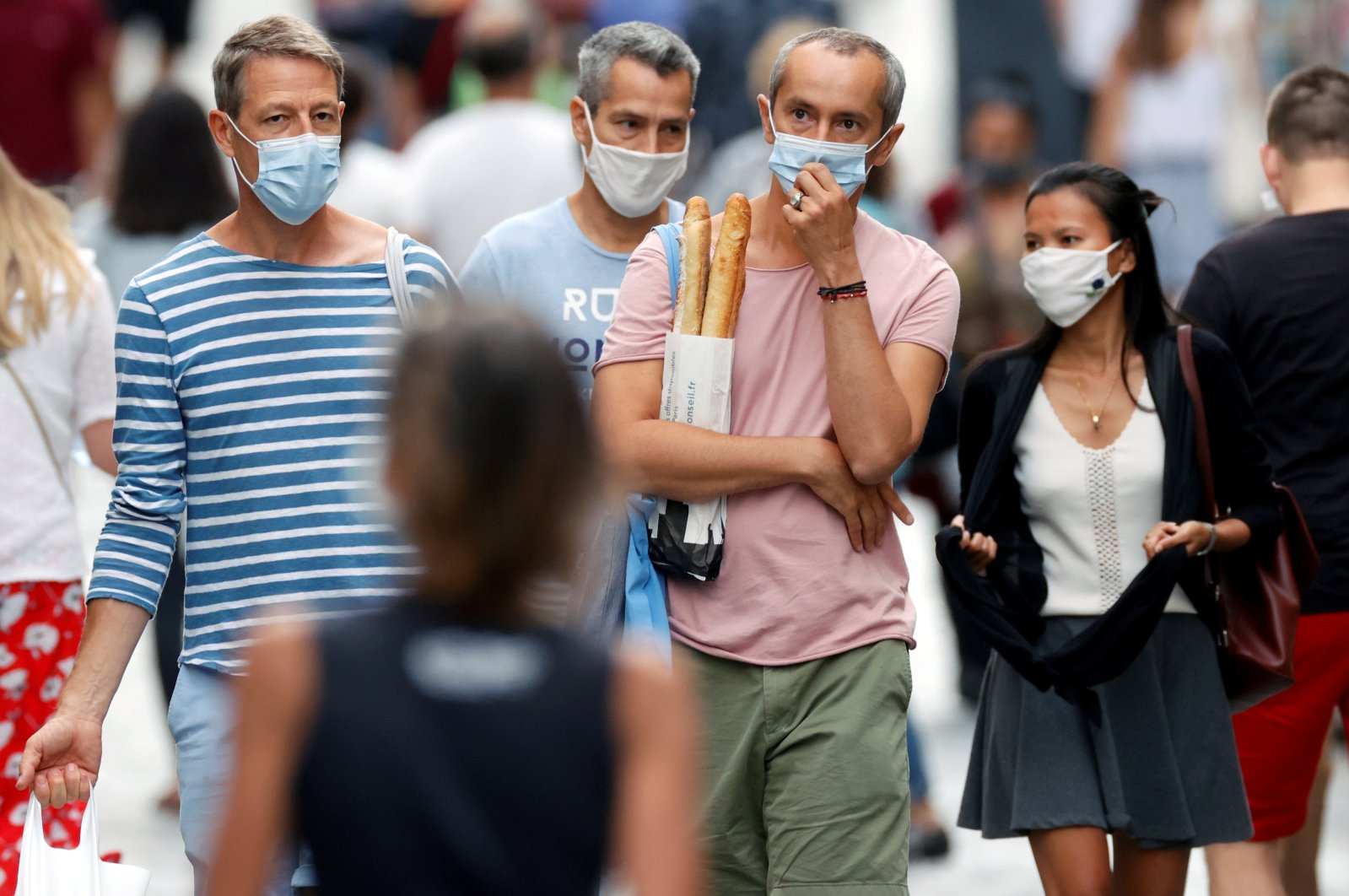 People wearing protective masks walk on Rue Montorgueil in Paris, France, Aug. 22, 2020. (Reuters Photo)