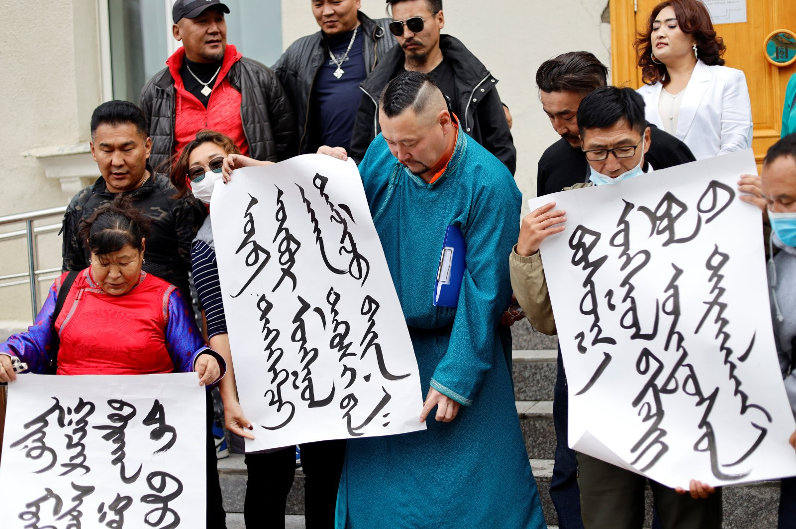 Demonstrators, holding signs with Mongolian script, protest against China's changes to school curriculums that remove Mongolian language from core subjects, outside the Mongolian Ministry of Foreign Affairs in Ulaanbaatar, Mongolia, Aug. 31, 2020. (Reuters Photo)