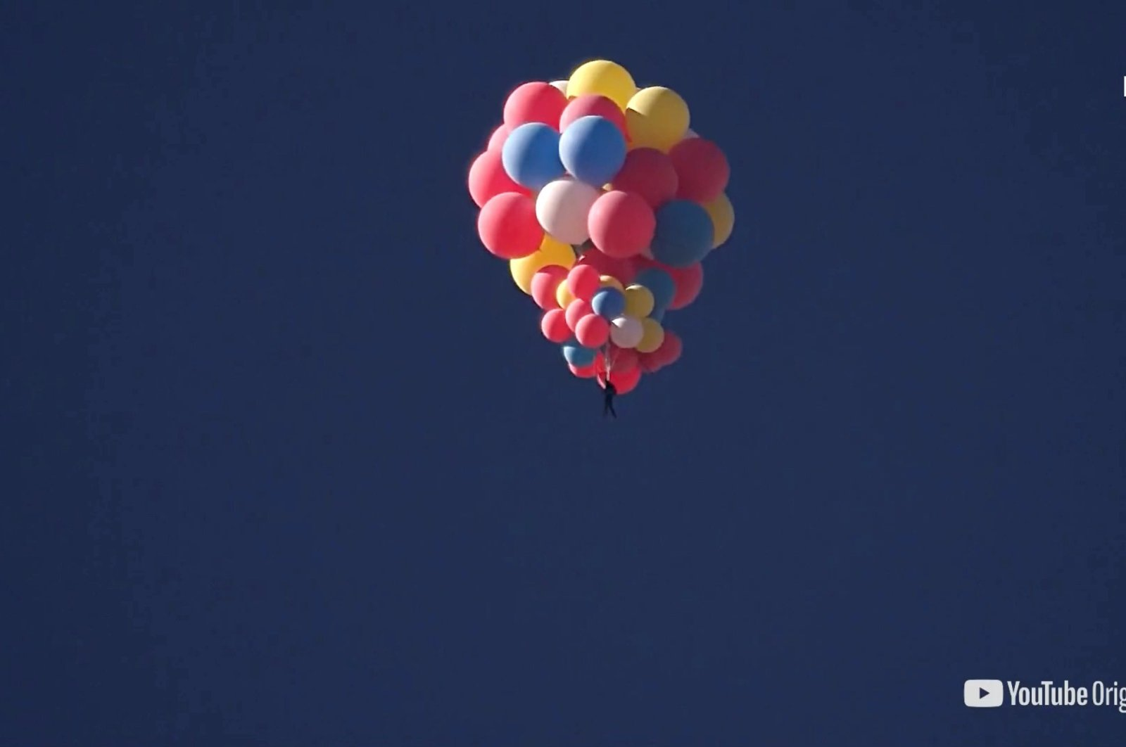 Extreme performer David Blaine hangs with a parachute under a cluster of balloons during a stunt to fly thousands of feet into the air, in a still image from video taken over Page, Arizona, U.S., Sept. 2, 2020. (David Blaine handout via Reuters)
