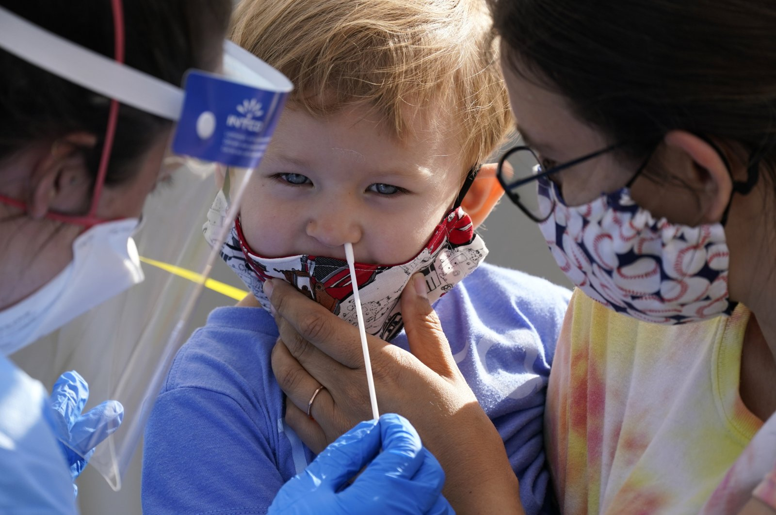 Penny Brown, 2, is held by her mother, Heather Brown, as her nose is lightly swabbed during a test for COVID-19 at a new walk-up testing site at Chief Sealth High School, in Seattle, Washington, Aug. 28, 2020. (AP Photo)