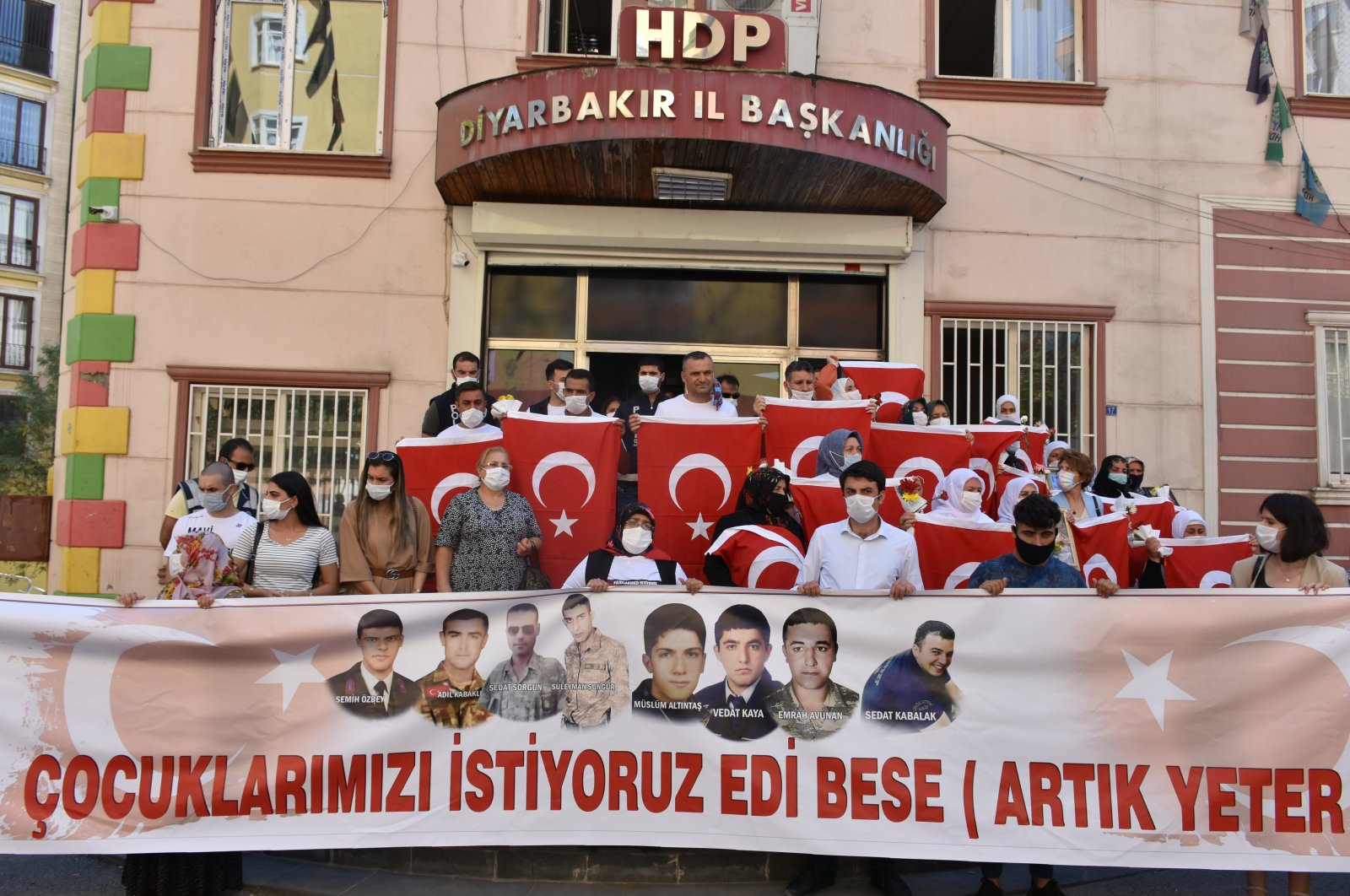 """Families protesting PKK in front of the HDP headquarters in Diyarbakır hold a banner with the pictures of kidnapped children and writing saying """"We want our children back, enough"""" on it, Sept. 3, 2020. (AA)"""