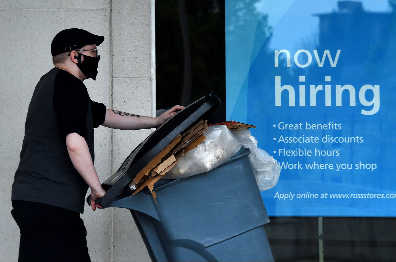 "A man wearing a face mask walks past a ""Now Hiring"" sign in front of a store amid the coronavirus pandemic in Arlington, Virginia, U.S., May 14, 2020. (AFP Photo)"