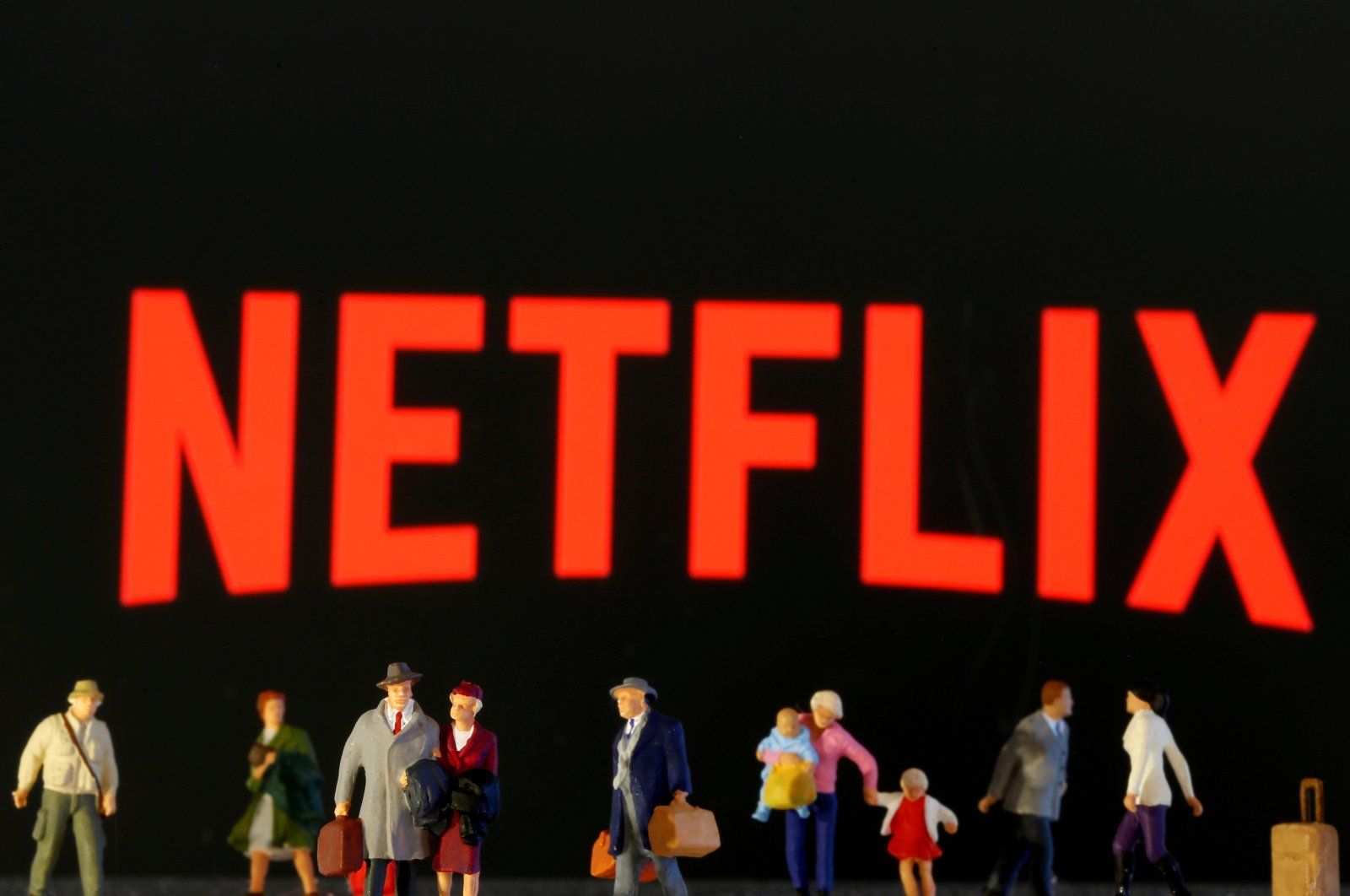 This illustration shows small toy figures in front of the Netflix logo. (Reuters Photo)