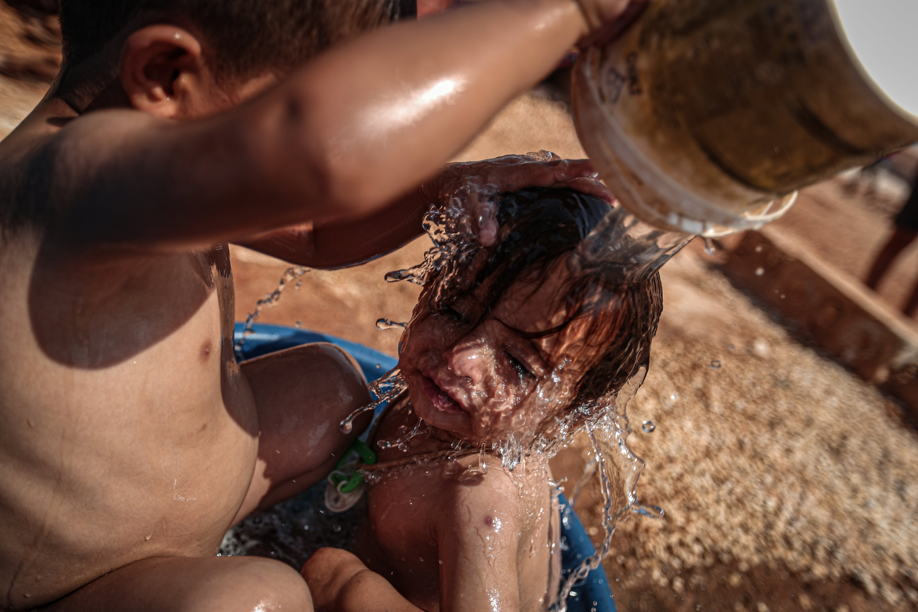 Fed up with the heat, Syrian refugee children find a solution by dousing each other with water from head to toe, Idlib, Sept.3, 2020. (AA)