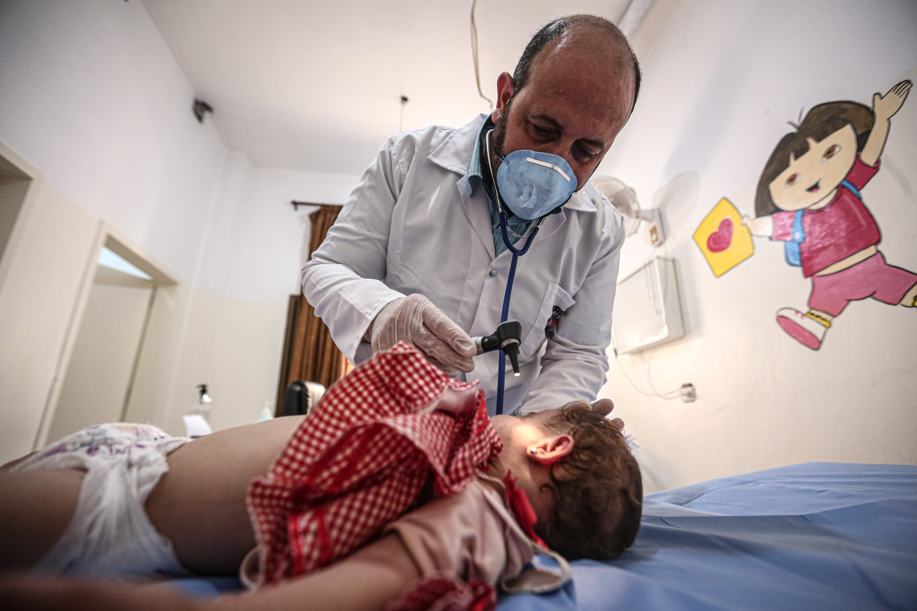 Mamoun Sahar, a doctor working at the Ibni Sina Child Hospital, takes care of a child patient hospitalized with heat-related symptoms, Idlib, Sept.3, 2020. (AA)