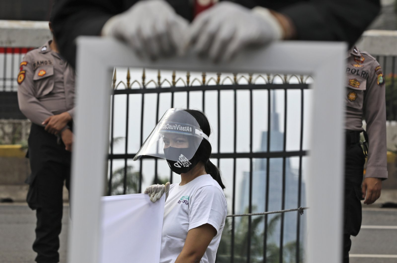 A mirror reflects the image of an activist wearing a mask and protective face shield as a precaution against the coronavirus outbreak in Jakarta, Indonesia, July 14, 2020. (AP Photo)