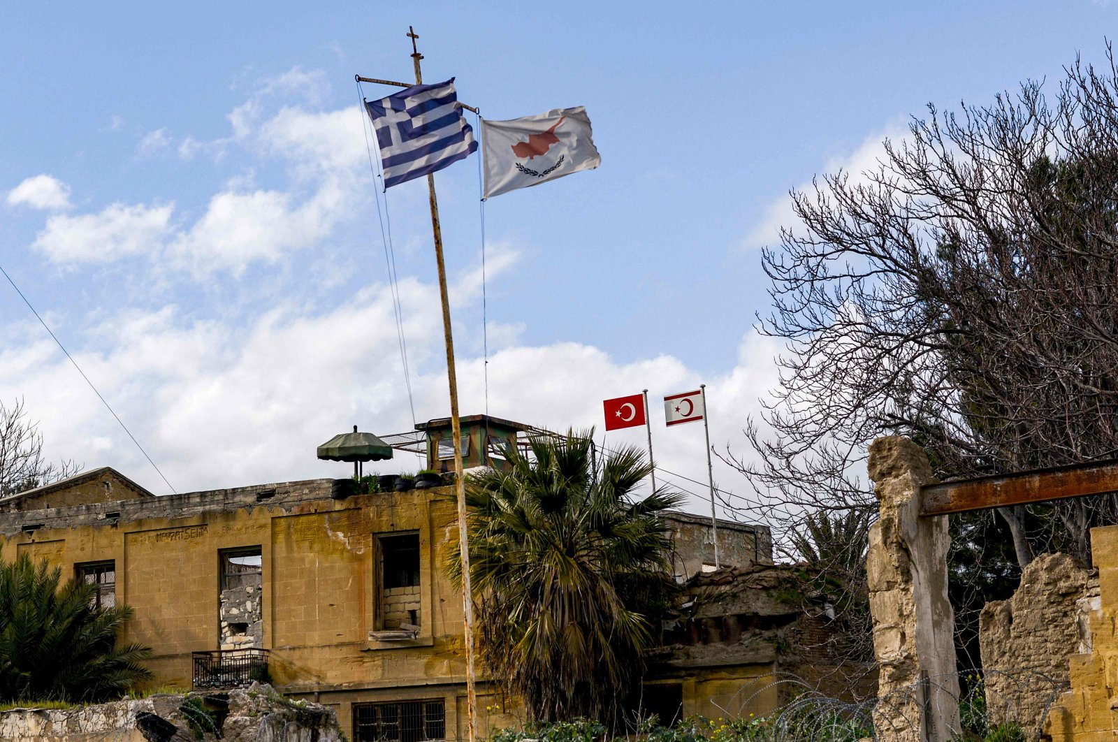 A  view of (L to R, foreground) the flags of Greece, the Greek Cypriot administration, (L to R, background) Turkey, and the Turkish Republic of Northern Cyprus (TRNC) flying on respective security outposts lying off both sides of the United Nations Buffer Zone in the old walled city of the divided capital Nicosia, Feb. 7, 2020. (AFP Photo)