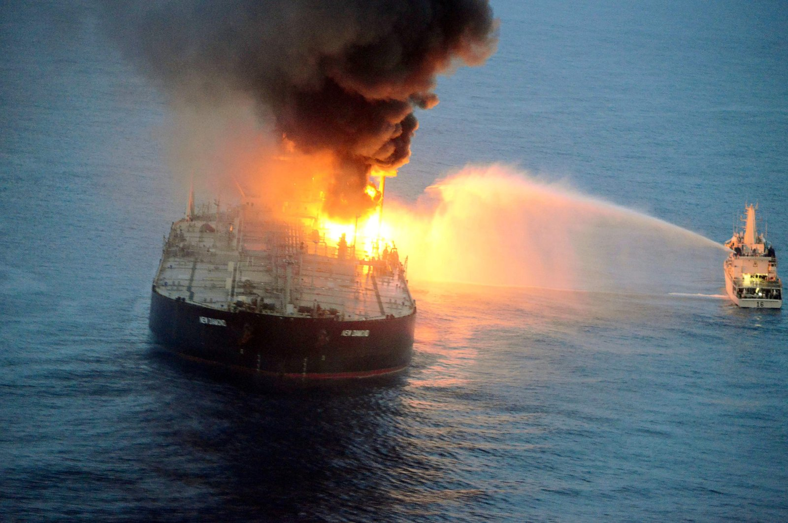 This handout photograph taken on Sept. 4, 2020, and released by the Sri Lanka Air Force, shows an Indian coast guard ship (R) battling to extinguish the fire on the Panamanian-registered crude oil tanker New Diamond, some 60 kilometers off Sri Lanka's eastern coast. (Sri Lankan Air Force Photo via AFP)