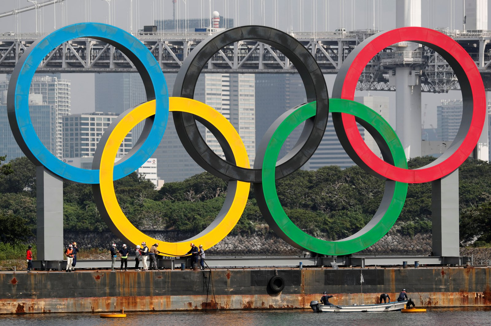 Workers prepare to carry the giant Olympic rings, which are being temporarily removed for maintenance, at the waterfront area at Odaiba Marine Park in Tokyo, Japan, Aug. 6, 2020. (Reuters Photo)
