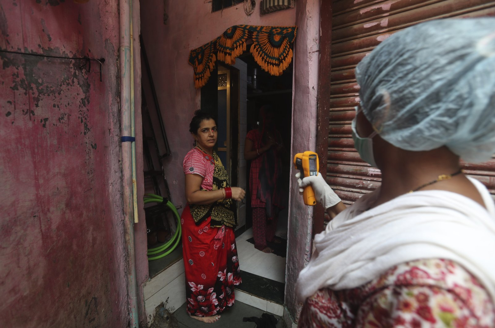 A health worker screens people for symptoms of COVID-19 in Dharavi, one of Asia's biggest slums, in Mumbai, India, Sept. 4, 2020. (AP Photo)