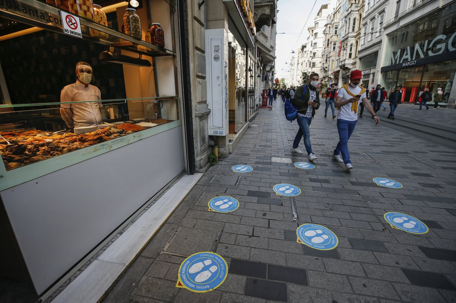 Signs, for customers to observe social-distancing measures, are seen on the road as a restaurant worker wearing a protective face mask and shield against the spread of coronavirus, waits for customers at a restaurant on Istiklal street, the main shopping street in Istanbul, June 1, 2020. (AP Photo)