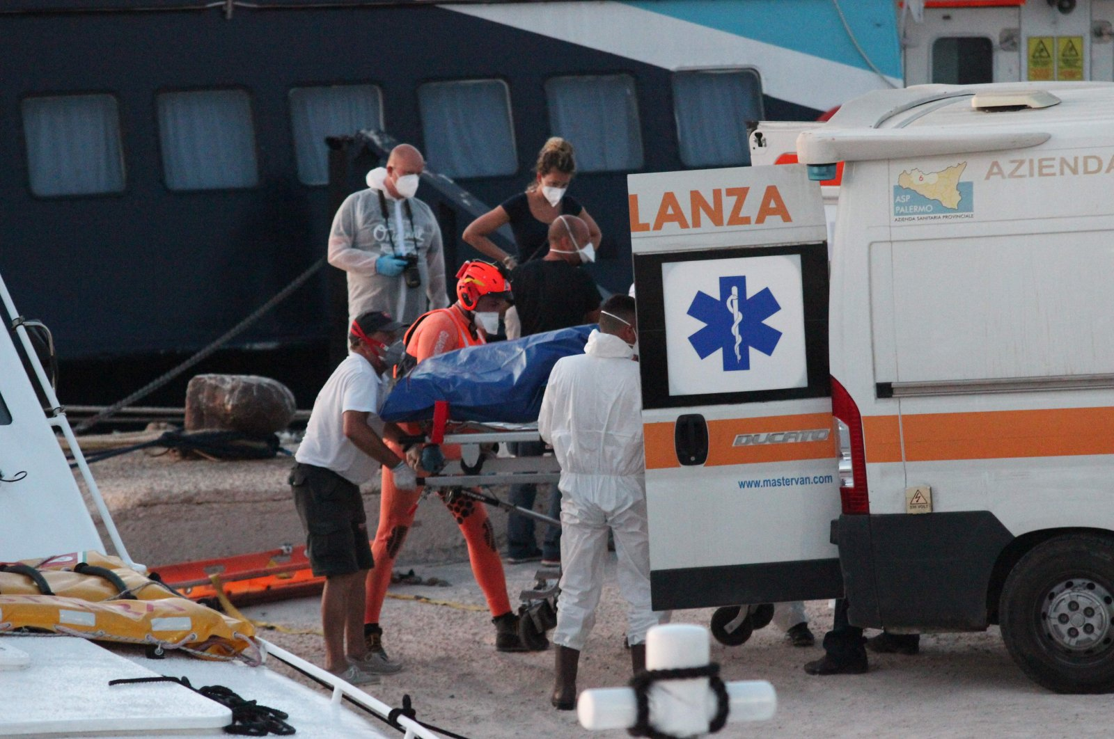 """The body of a dead migrant wrapped in a blue bag is being put into an ambulance, after some 49 rescued migrants arrived at the commercial port of Lampedusa from the Coast Guard patrol boat """"CP-319"""" (Rear R), which transhipped rescued migrants from the civilian rescue boat """"Louise Michel"""" 80 kilometers southeast of the Italian pelagic island, Aug. 29, 2020.  (AFP Photo)"""