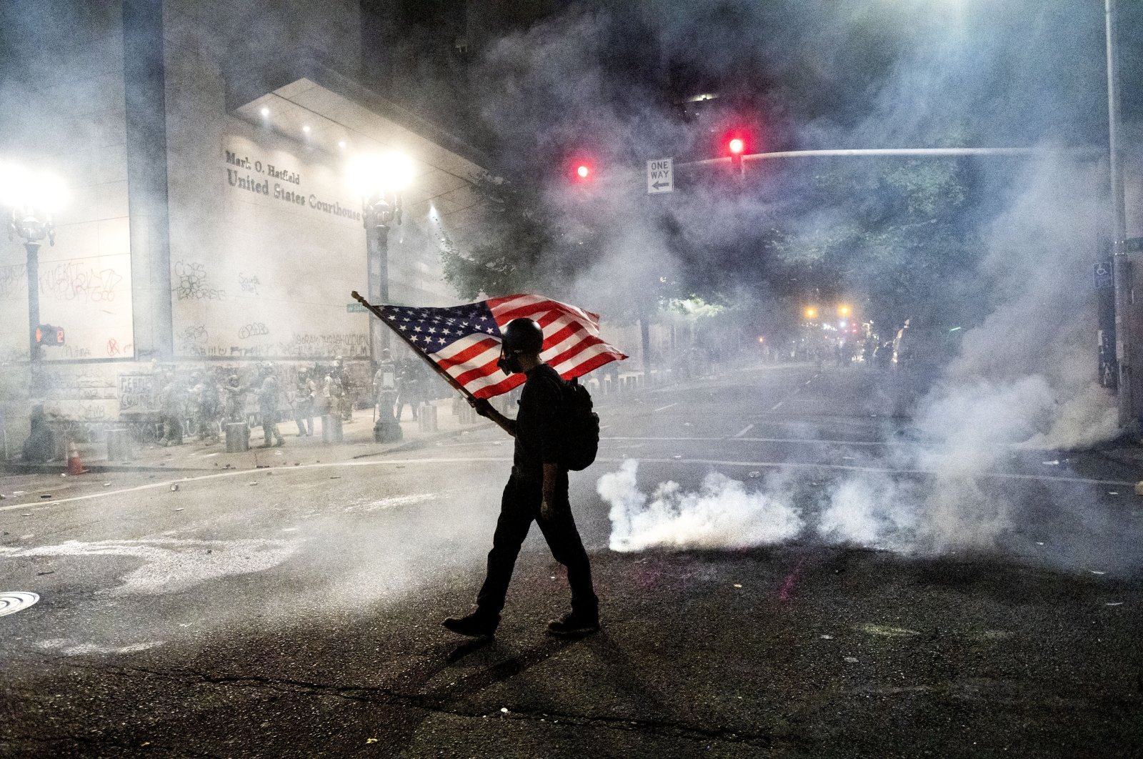 A Black Lives Matter protester carries an American flag as teargas fills the air outside the Mark O. Hatfield United States Courthouse, Portland, Oregon, July 21, 2020. (AP Photo)