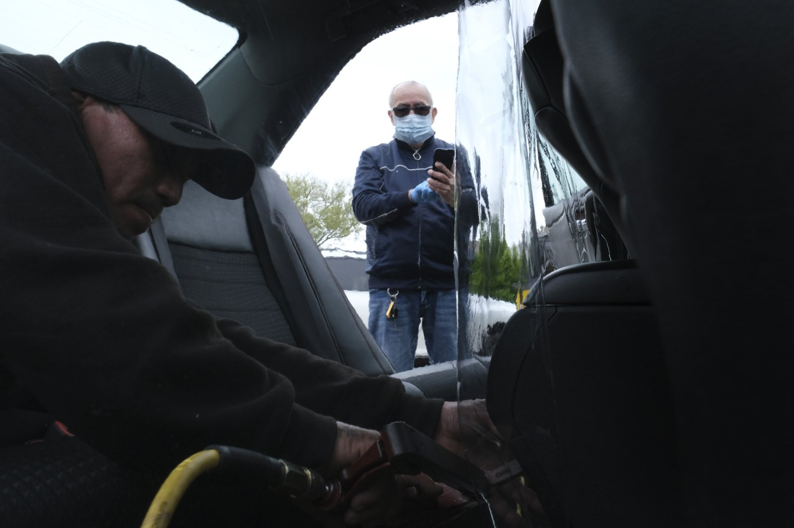 Luis Hidalgo, wearing a face mask, watches as Joel Rios installs a plastic barrier in his car to protect himself and his passengers from the new coronavirus in the Bronx borough of New York, U.S., May 6, 2020. (AP Photo)